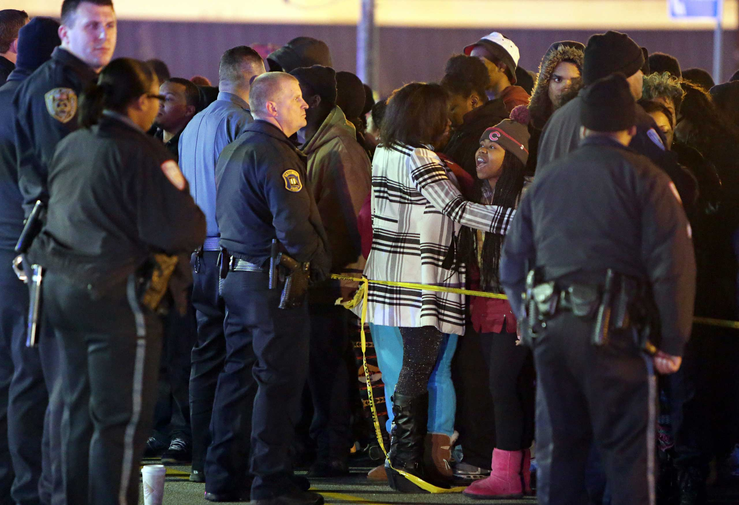 Police hold back a crowd at the perimeter of a scene on Dec. 24, 2014, following a shooting at a gas station in Berkeley, Mo.