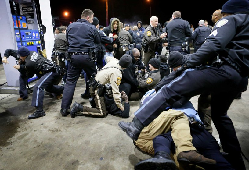 Police try to control a crowd on Dec. 24, 2014, on the lot of a gas station following a shooting Tuesday in Berkeley, Mo.