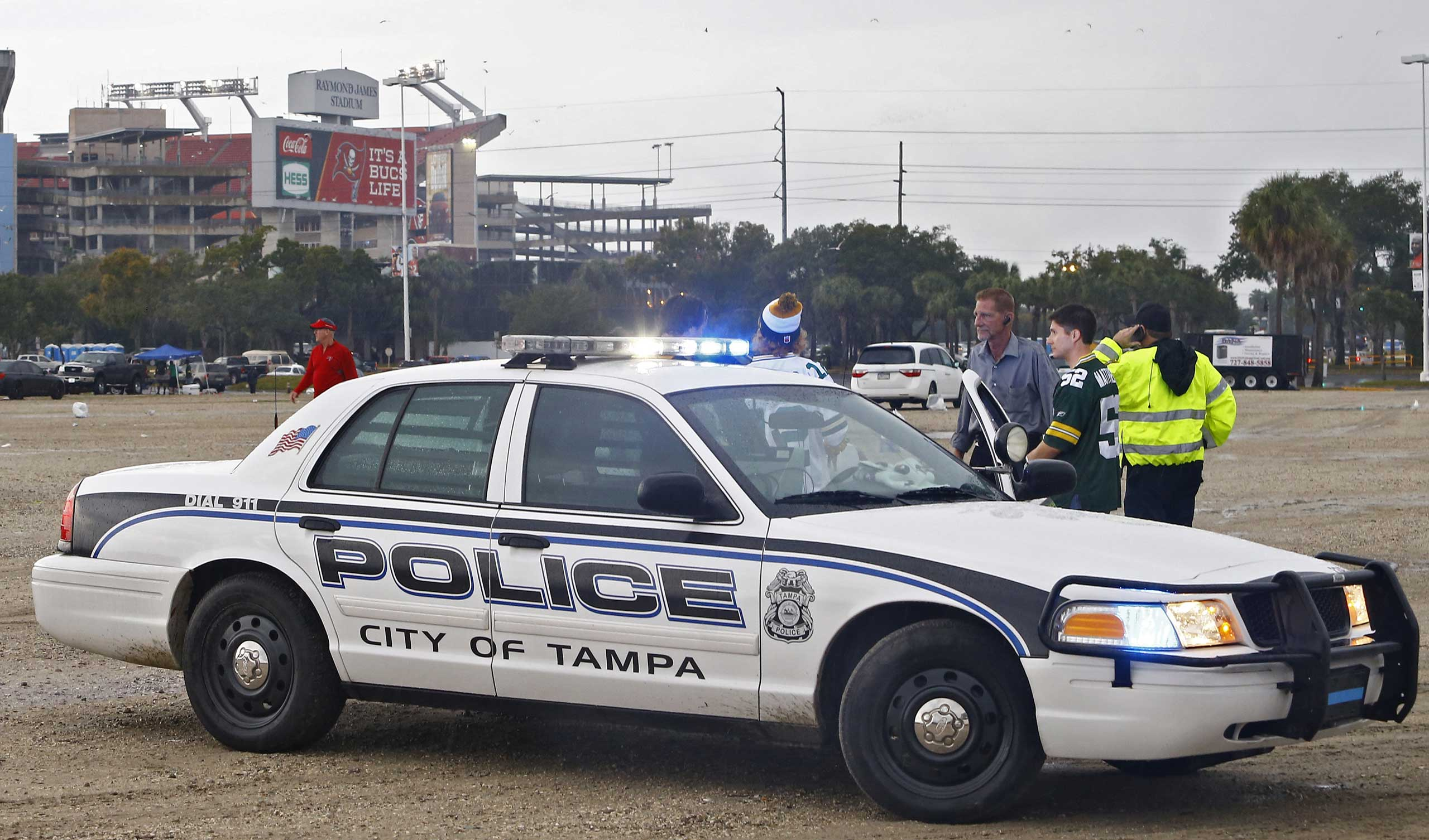 Tampa Police Officers talk to spectators after football fans were reportedly taken to the hospital with injuries after a lightning strike near the Raymond James Stadium, Dec. 21, 2014, in Tampa, Fla.