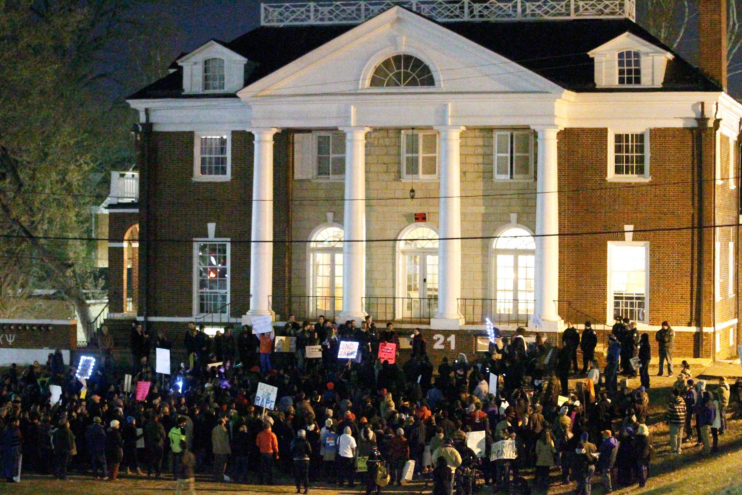 Protestors carry signs and chant slogans in front of the Phi Kappa Psi fraternity house at the University of Virginia, Nov. 22, 2014, in Charlottesville, Va.