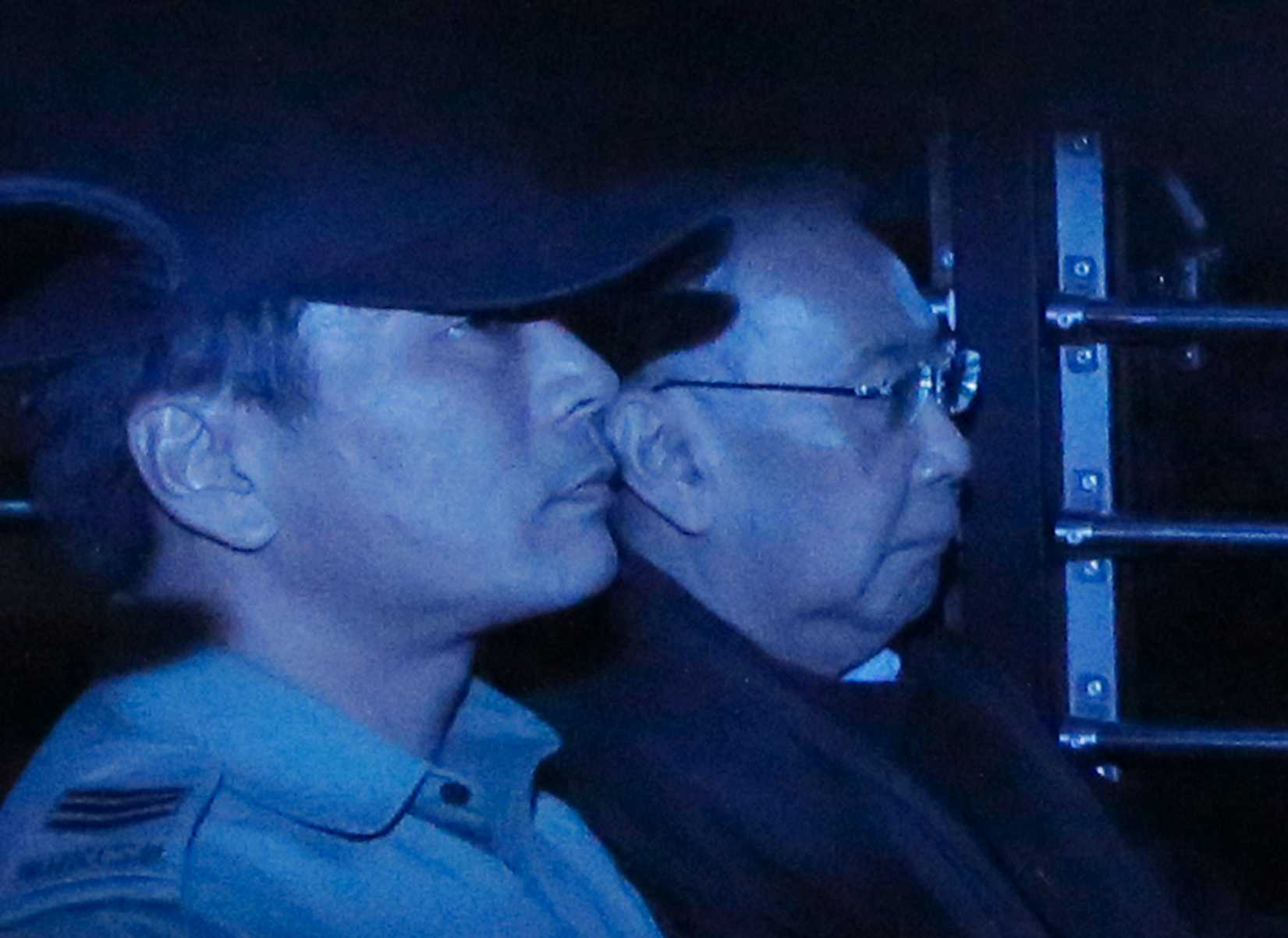 In this photo taken through a tinted glass, former Hong Kong Chief Secretary Rafael Hui, right, is escorted by a staff member from Hong Kong Correctional Services inside a van outside the High Court in Hong Kong on Dec. 19, 2014