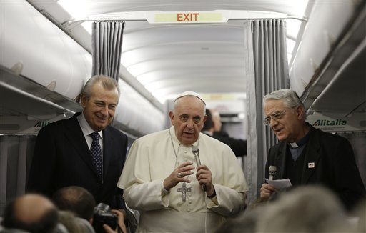 Pope Francis, center, talks during a press conference aboard the flight toward Rome on Nov. 30, 2014