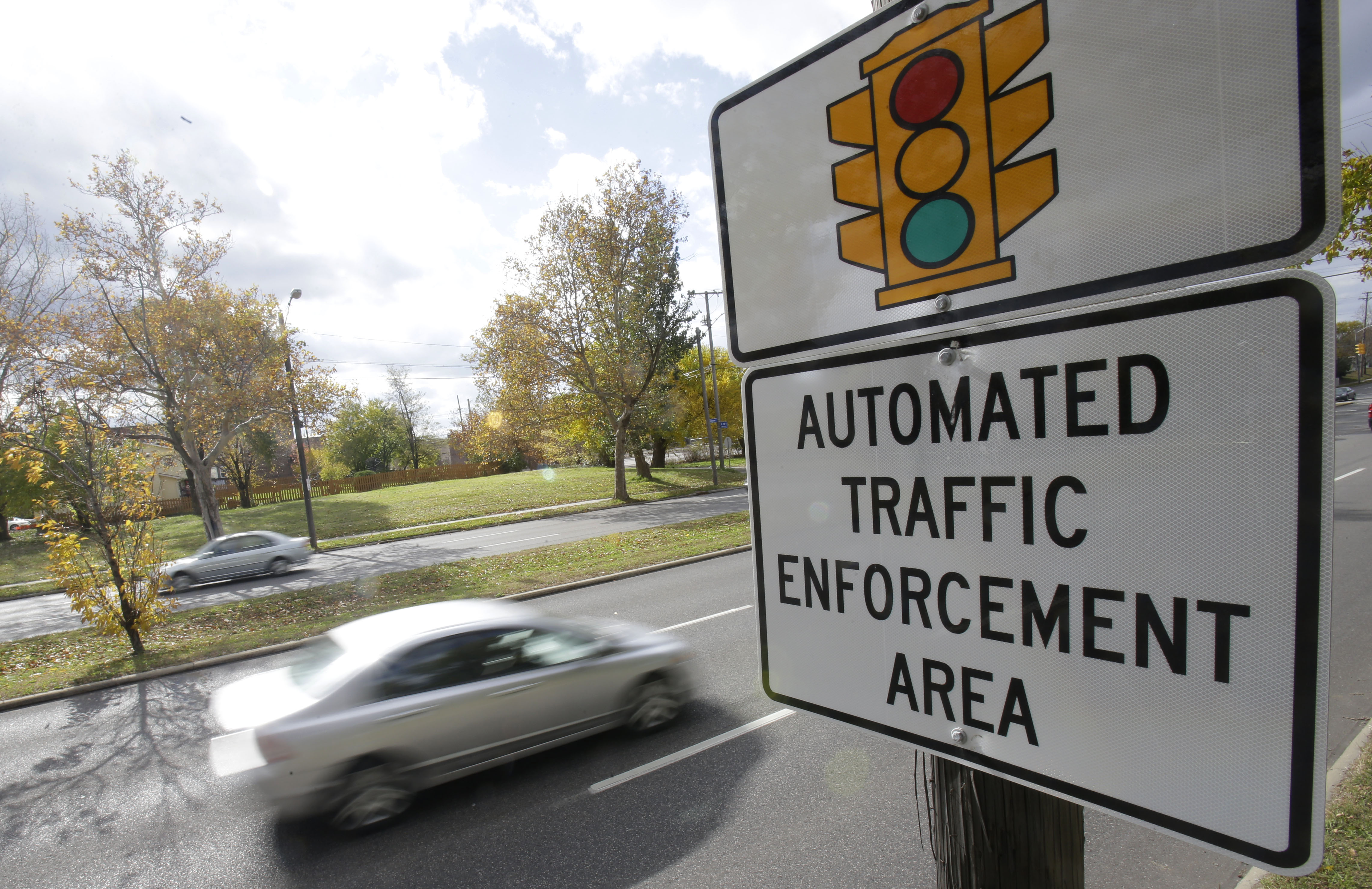 Motorists drive past a sign warning of upcoming traffic cameras on Oct. 29, 2014, in Cleveland, Ohio.