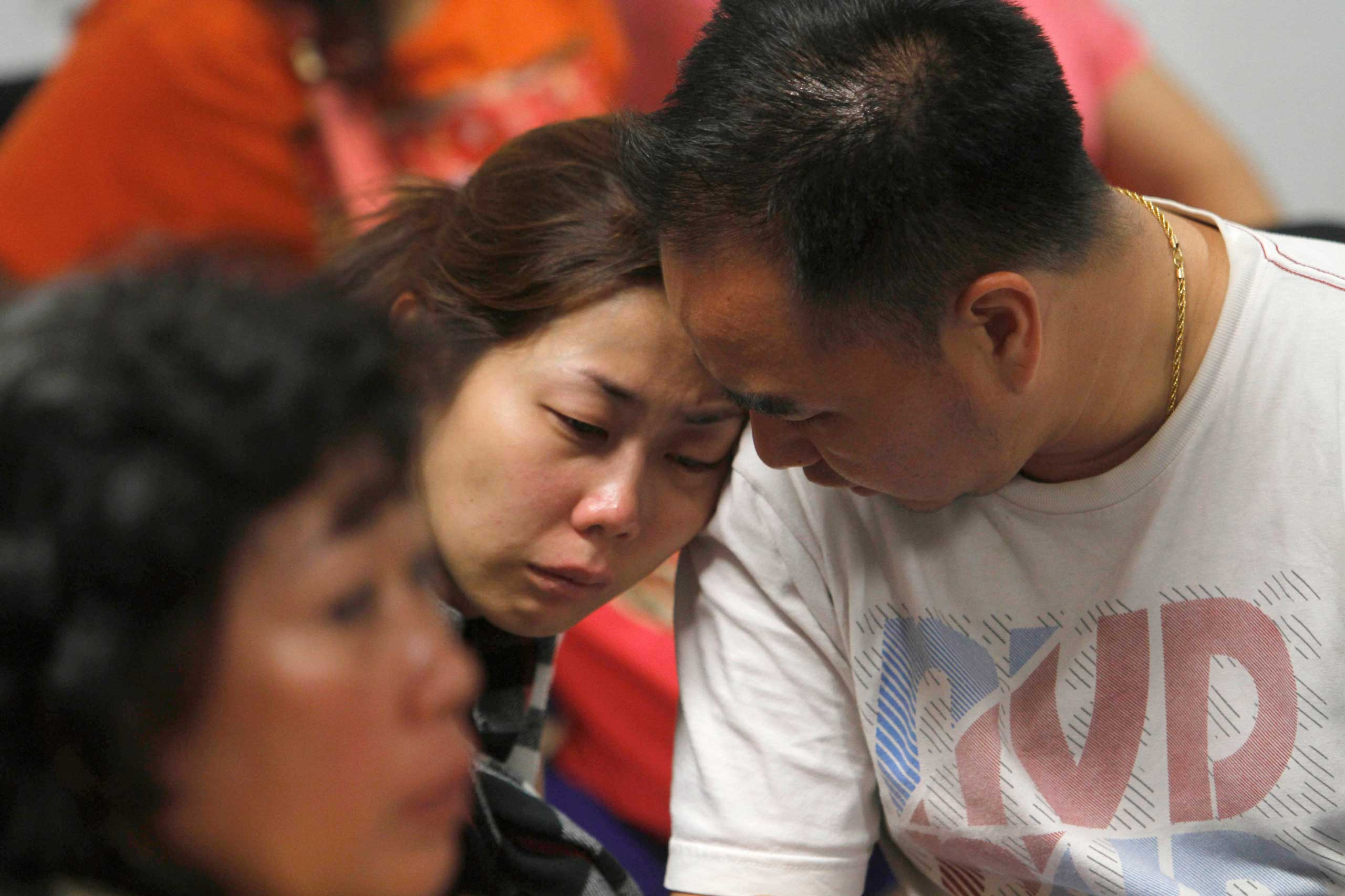 A relative of the passengers of AirAsia flight QZ8501 weeps as she waits for the latest news on the missing jetliner at a crisis center set up by local authority at Juanda International Airport in Surabaya, East Java, Indonesia, Dec. 28, 2014.