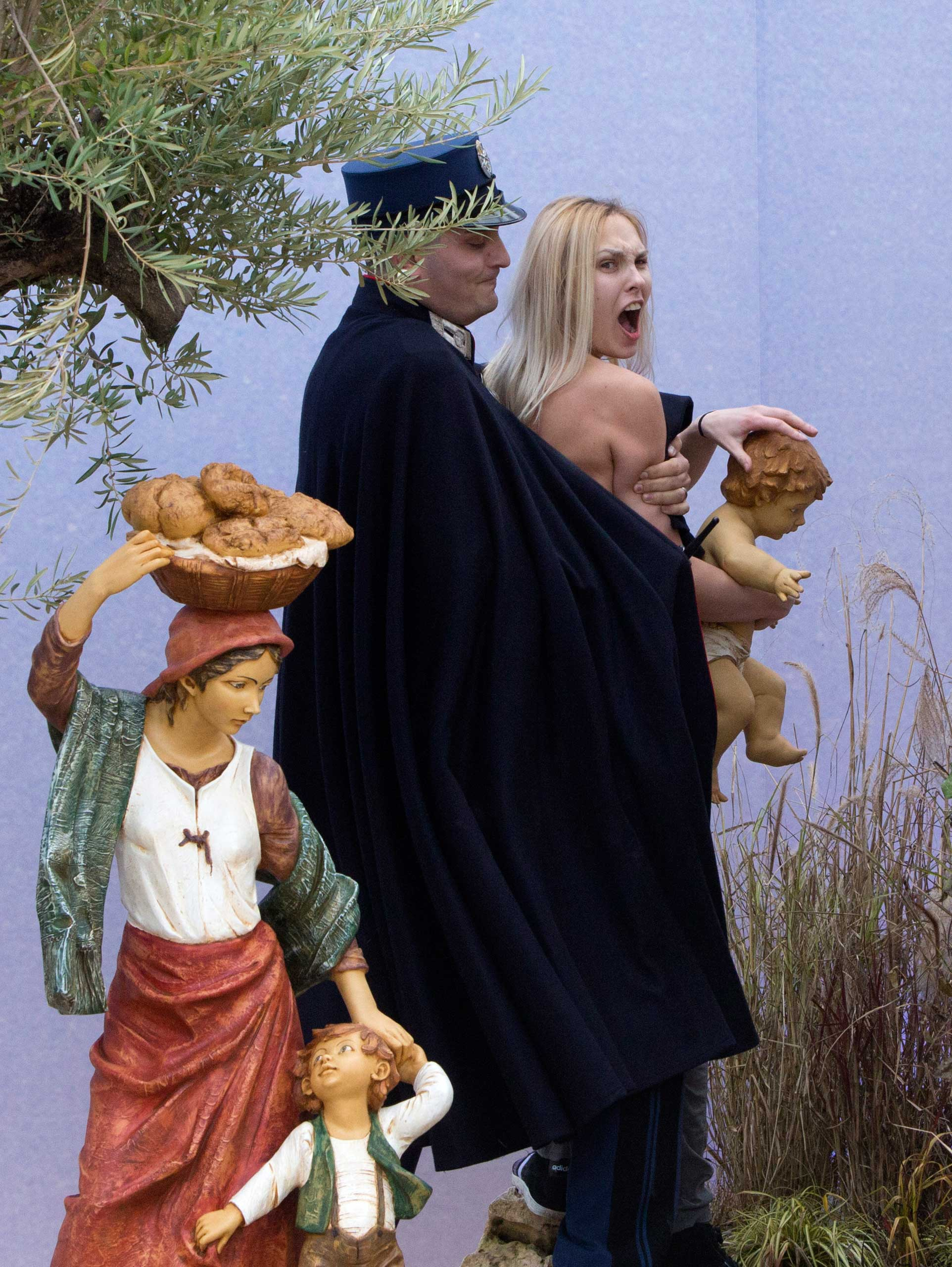 A gendarme from the Vatican's security forces stops a Ukrainian feminist group Femen activist after she snatched the statue of Baby Jesus from the Nativity scene set in St. Peter's Square at the Vatican, Dec. 25, 2014.
