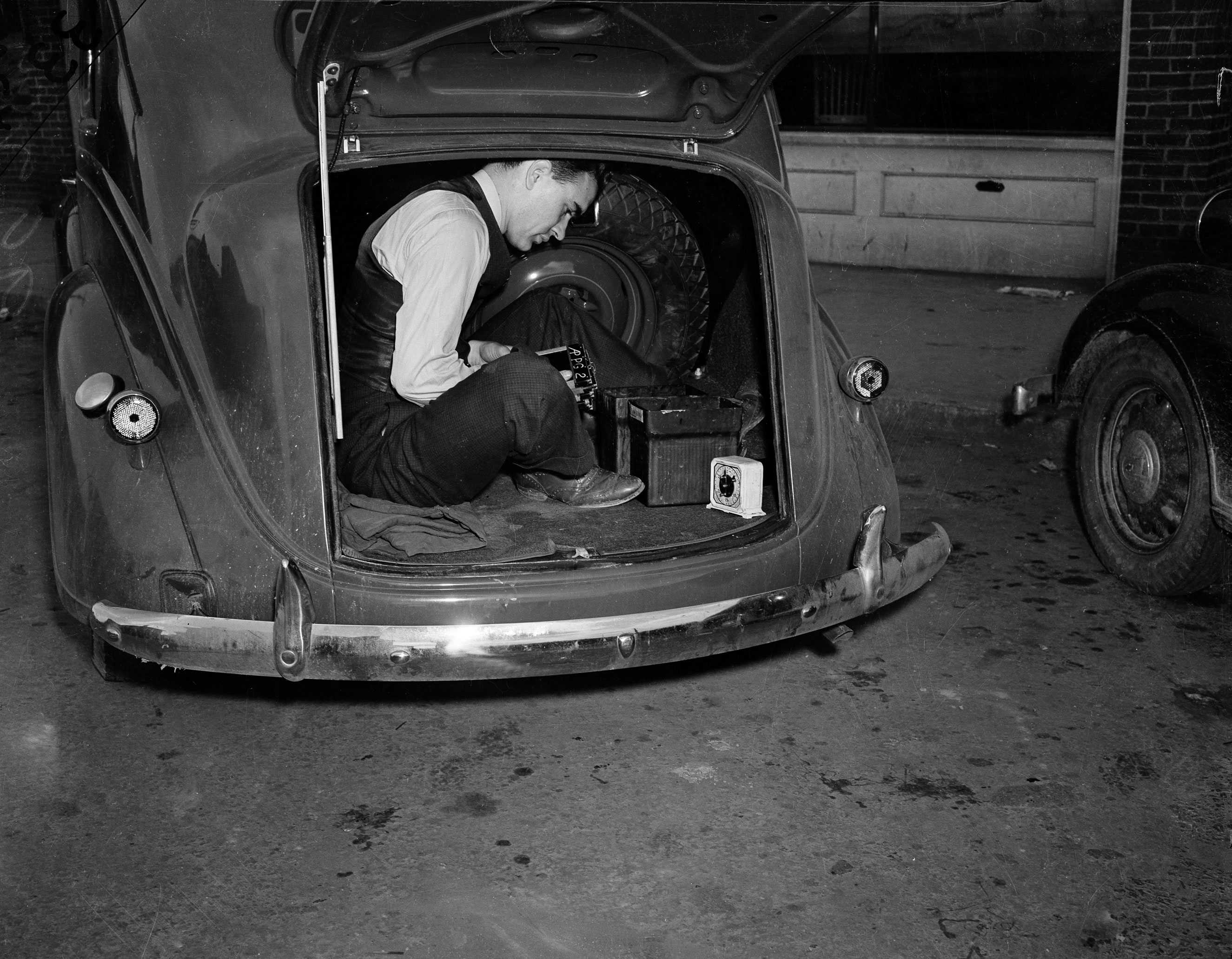 Photographer Bill Allen uses the trunk of his car as a darkroom to develop film coverage of a 1938 Virginia mine explosion.