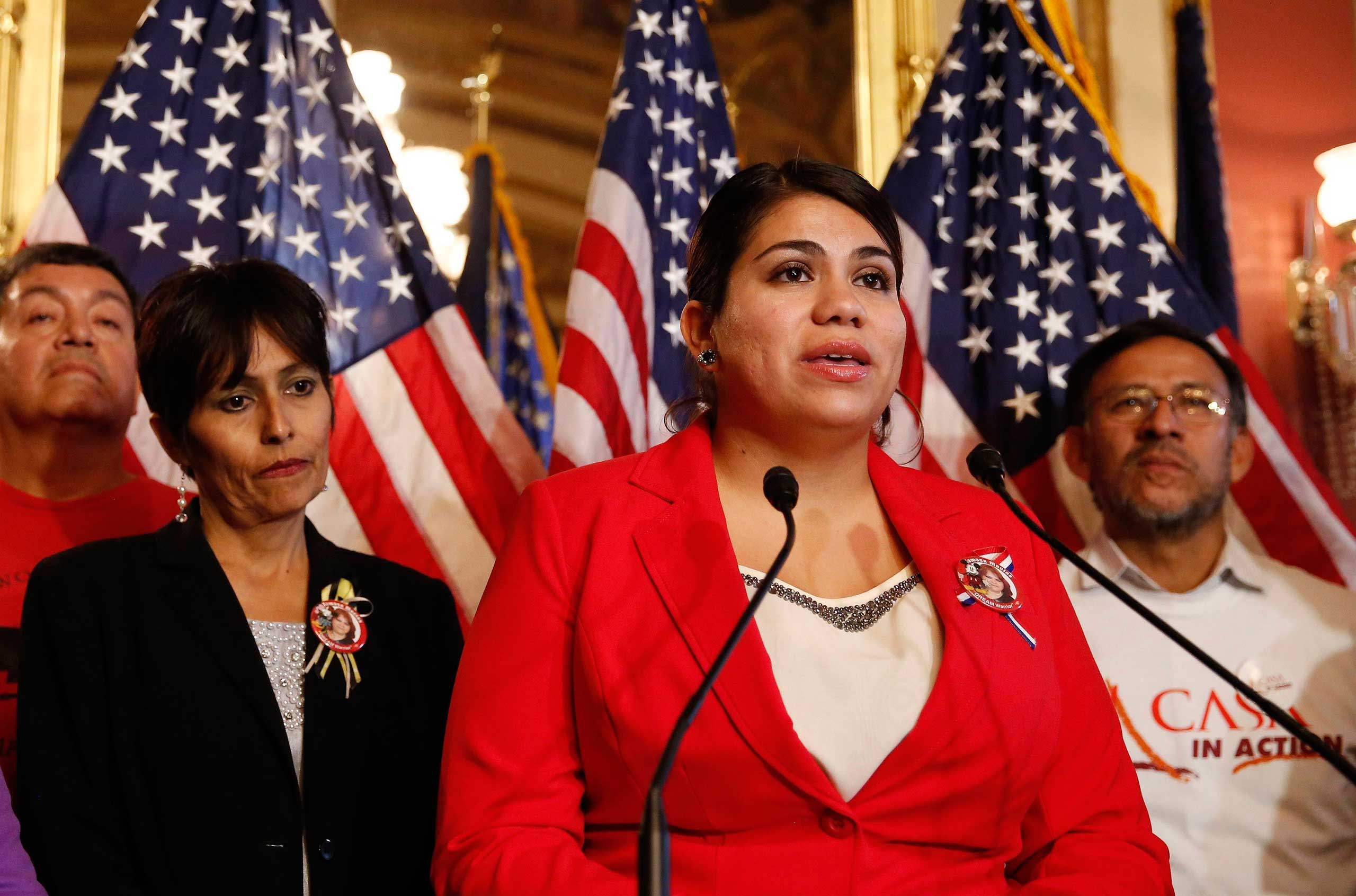 Immigration activist Astrid Silva (in red) stands next to her mother, Barbara Silva, as she speaks about immigration reform at a news conference on Capitol Hill in Washington, Dec. 10, 2014.