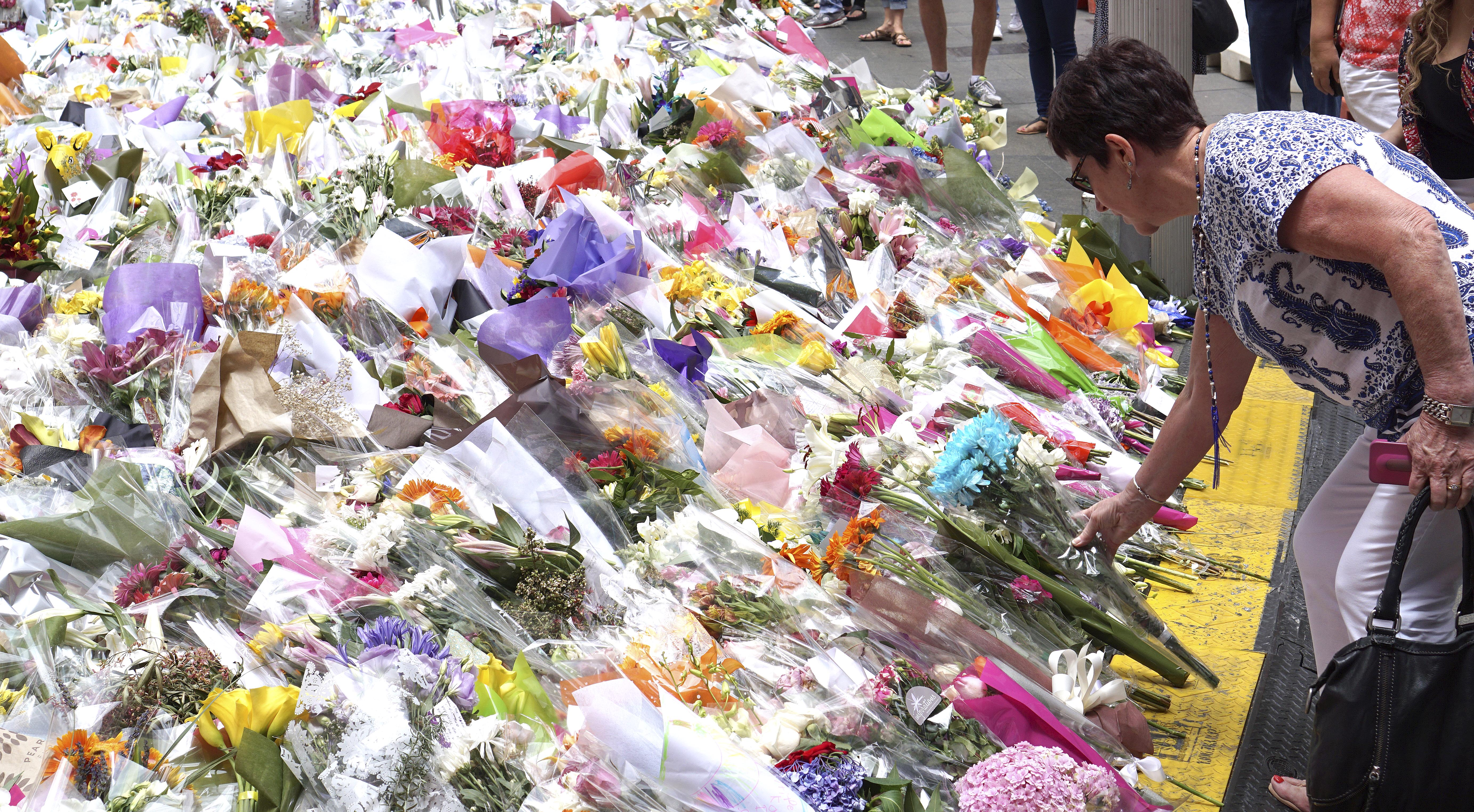A woman places a floral tribute at a temporary memorial site close to the Lindt Chocolat Cafe in Sydney, Australia, Friday, Dec. 19, 2014.