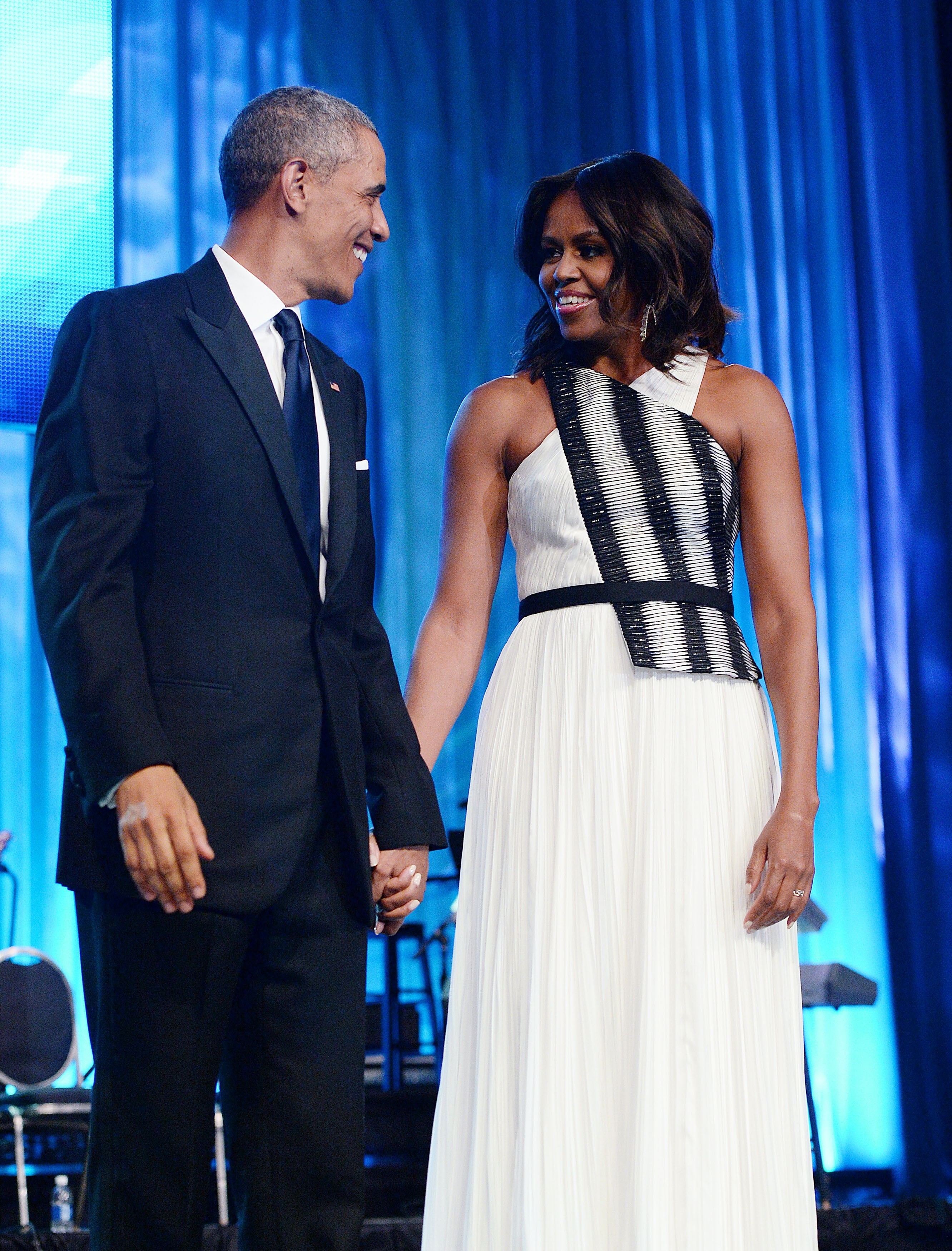 U.S. President Barack Obama and First Lady Michelle Obama arrive on stage for the Congressional Black Caucus Foundation Annual Phoenix Awards dinner, September 27, 2014 in Washington, DC.