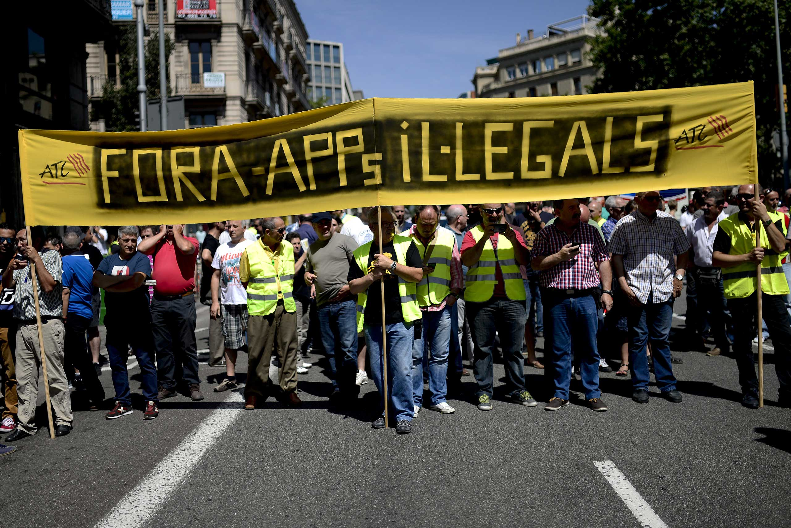 Taxi drivers hold a banner during a protest in Barcelona on June 11, 2014.