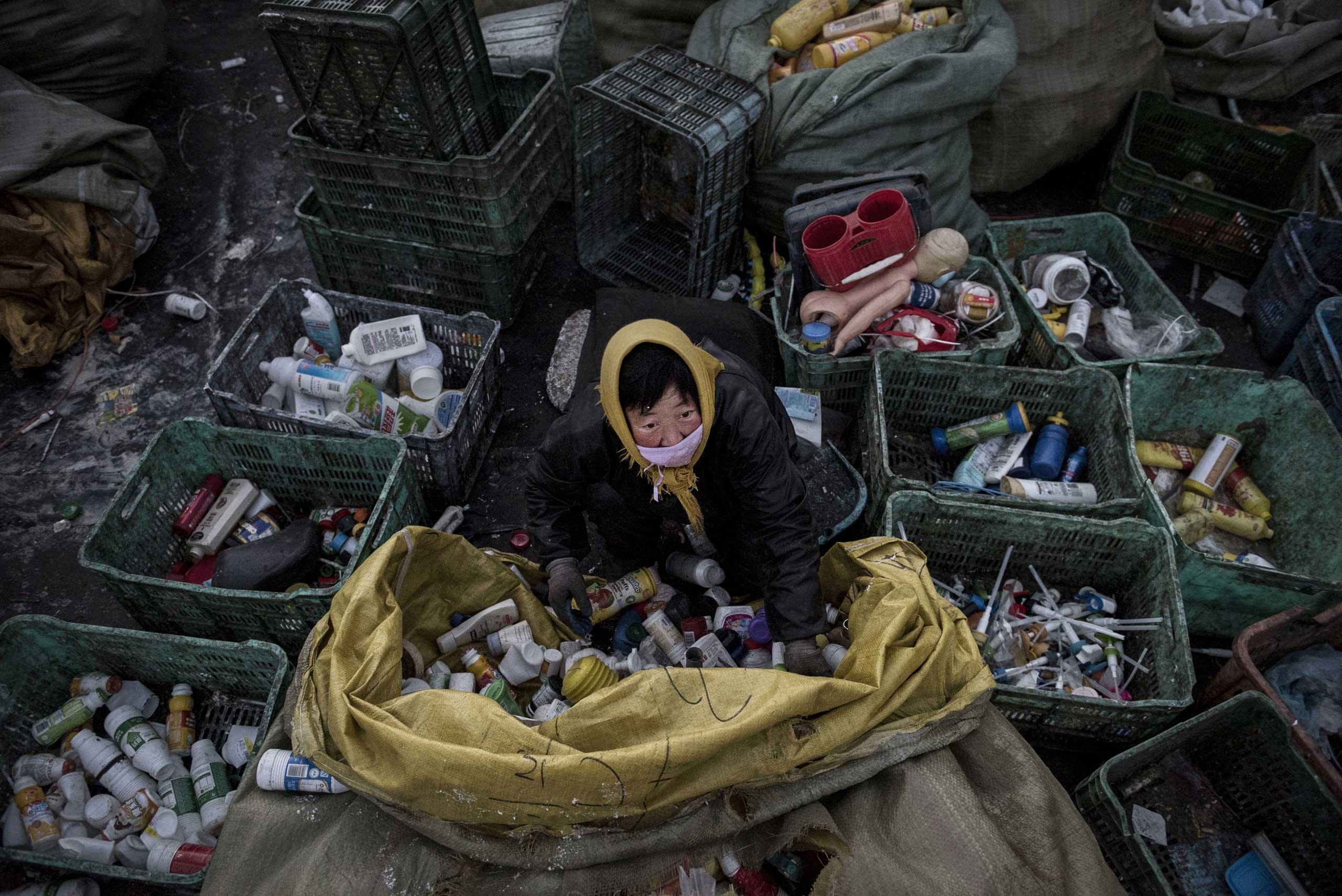 A laborer sorts plastic before being recycled in the Dong Xiao Kou village on Dec. 15, 2014 in Beijing.