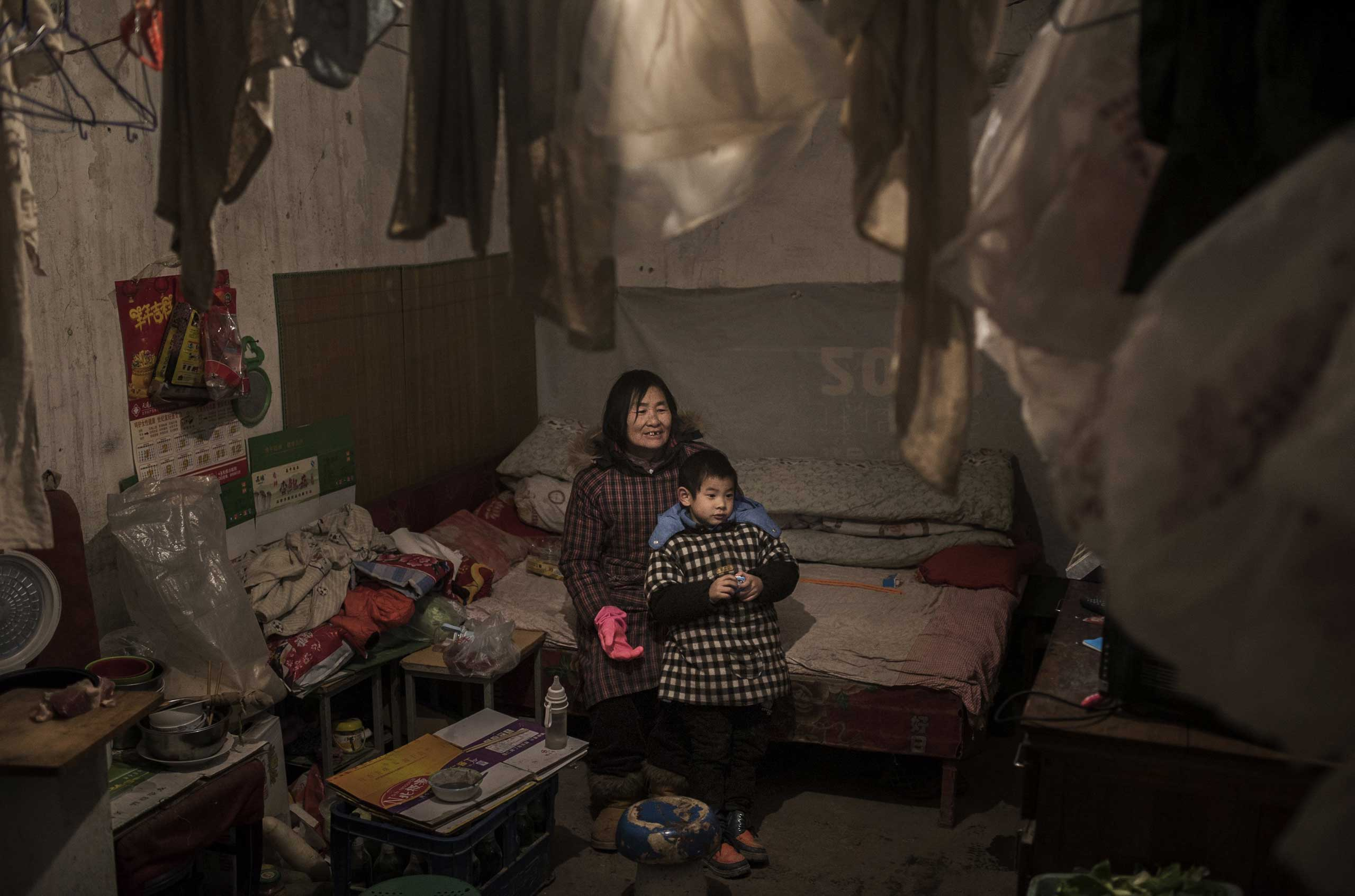 A laborer watches television with her grandson in the Dong Xiao Kou scrap village on Dec. 11, 2014 in Beijing.
