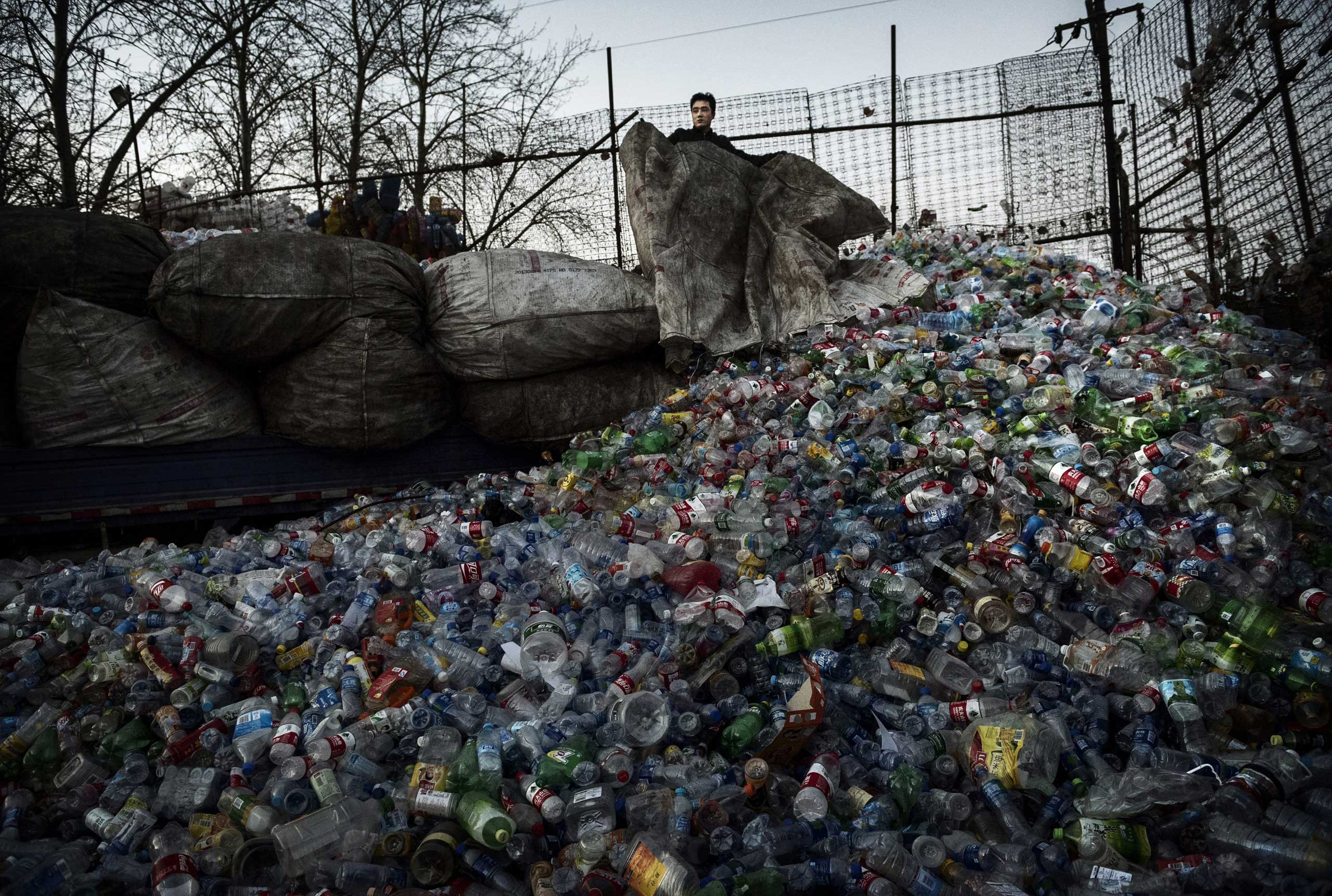 A laborer unloads plastic bottles to be recycled in the Dong Xiao Kou village on Dec. 12, 2014 in Beijing.