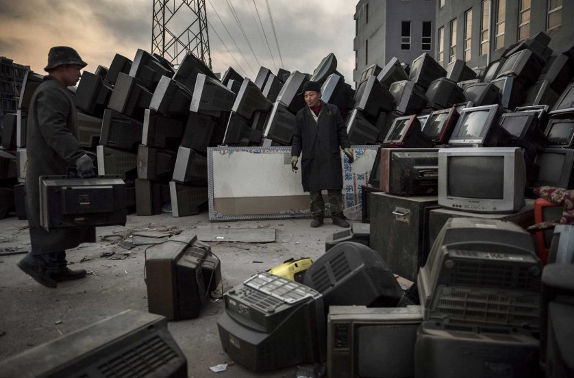 Laborers organize old televisions and computers to be recycled in the Dong Xiao Kou village on Dec. 11, 2014 in Beijing.