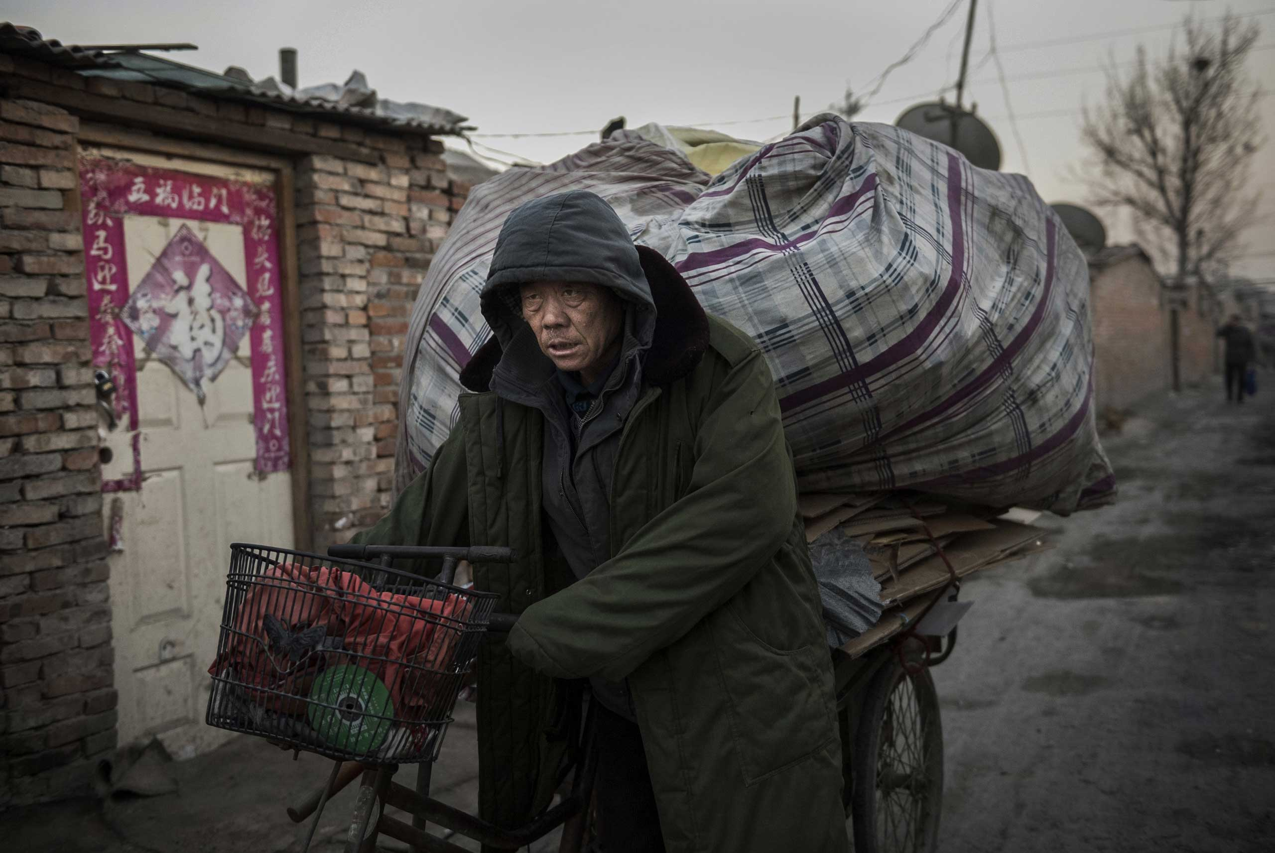 A laborer wheels goods collected to be recycled in the Dong Xiao Kou village on Dec. 11, 2014 in Beijing.