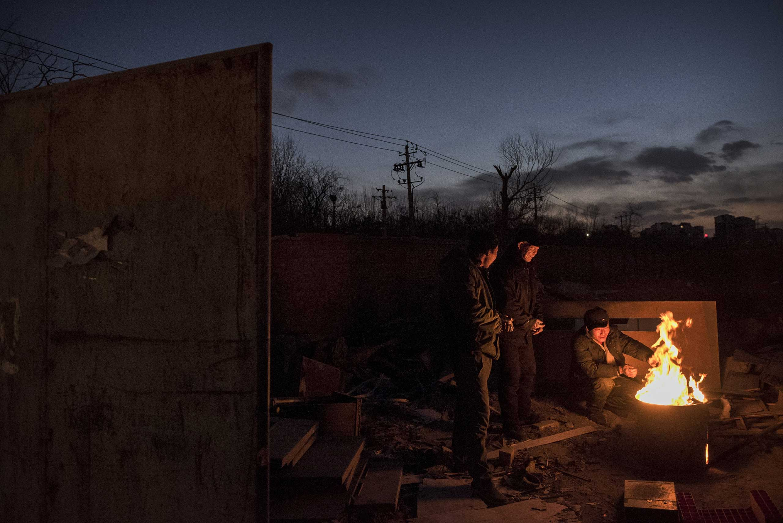 Laborers stay warm on a fire as they wait for goods to be recycled in the Dong Xiao Kou village on Dec. 12, 2014 in Beijing.