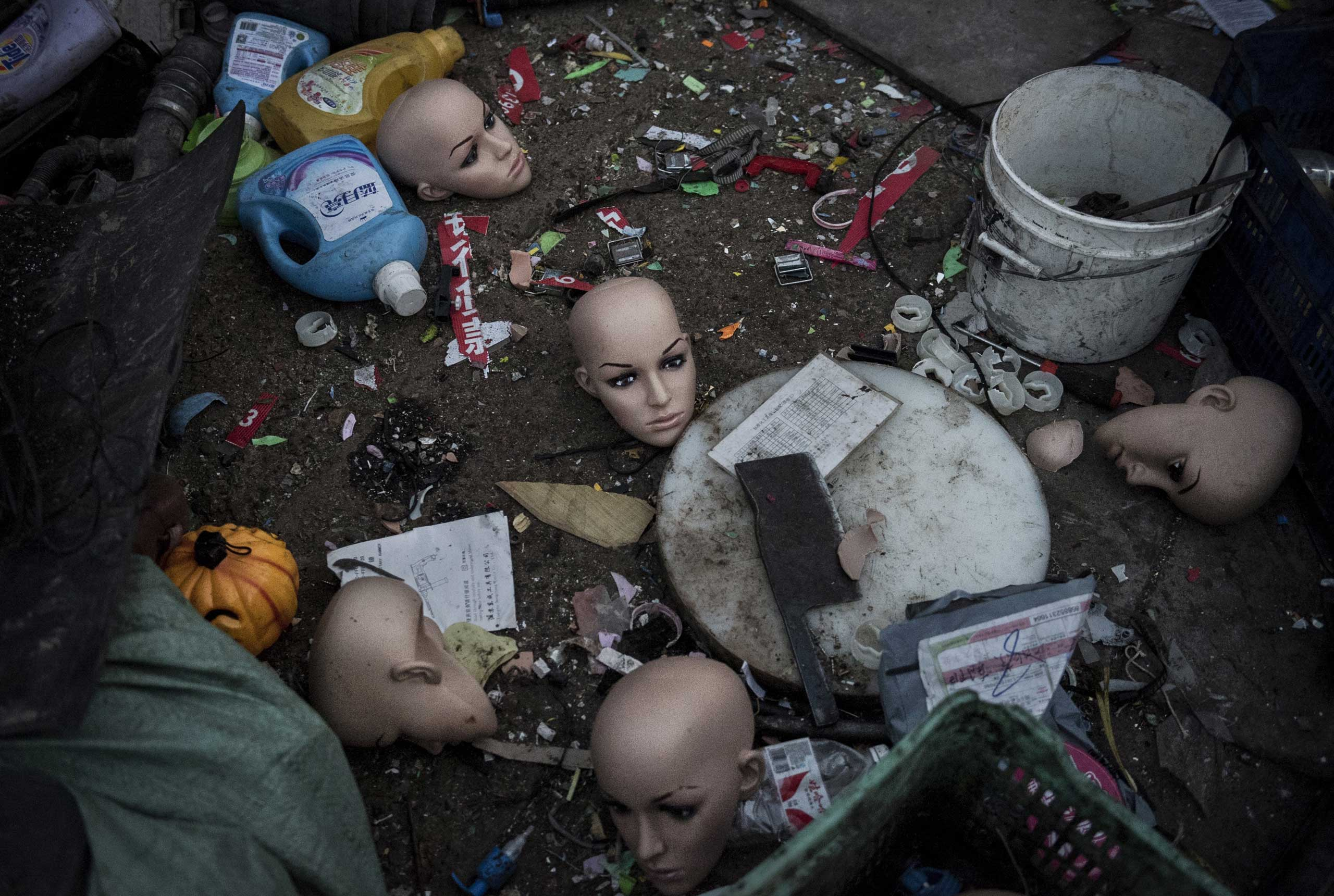 Plastic mannequin heads and other items lay on the ground before being recycled in the Dong Xiao Kou village on Dec. 15, 2014 in Beijing.