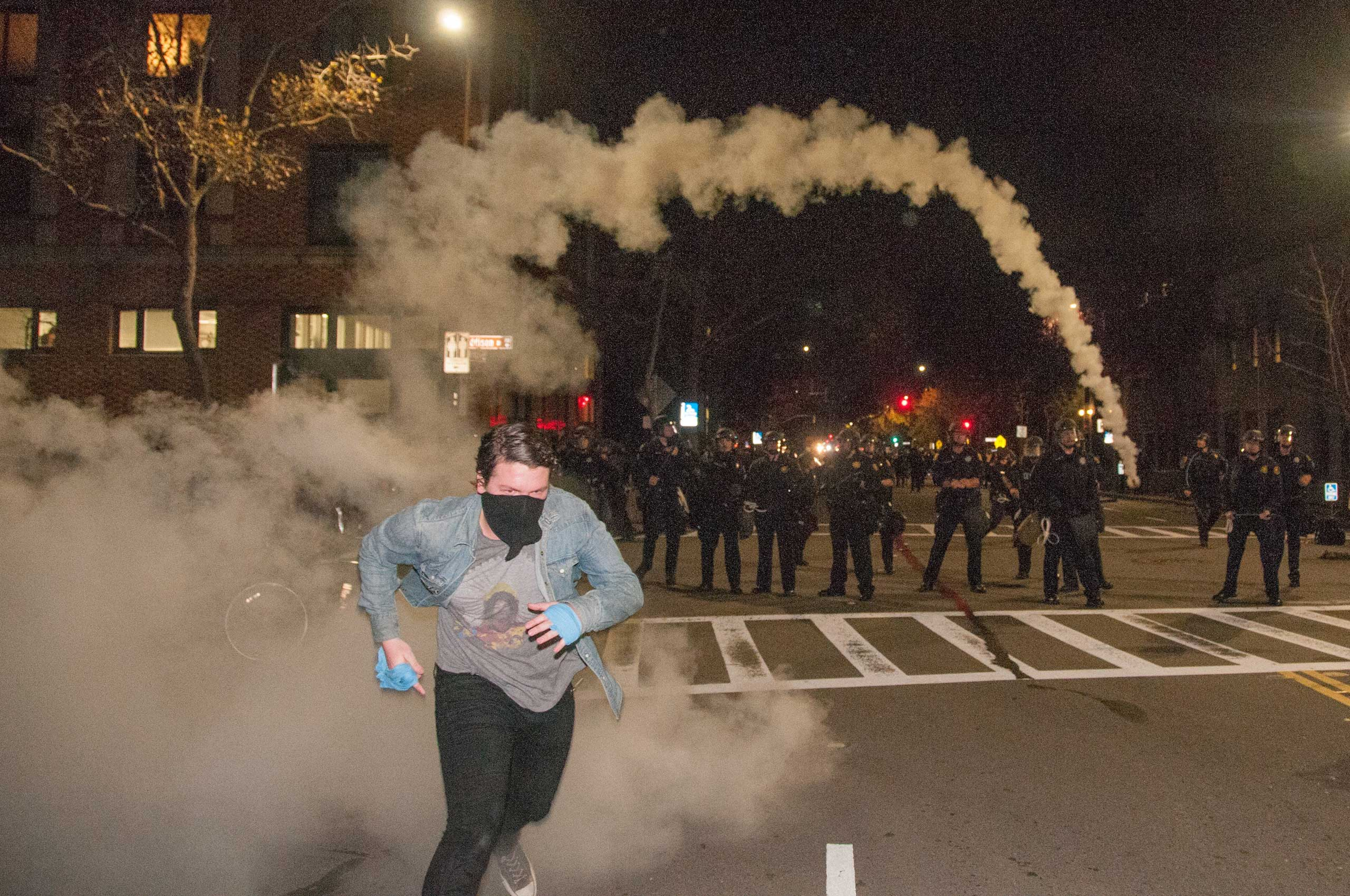 A protester runs after hurling back a smoke bomb, initially launched by police at demonstrators rallying against grand juries' decisions not to indict the police officers accused of killing Eric Garner and Michael Brown, Berkeley, Calif. on Dec. 6, 2014.