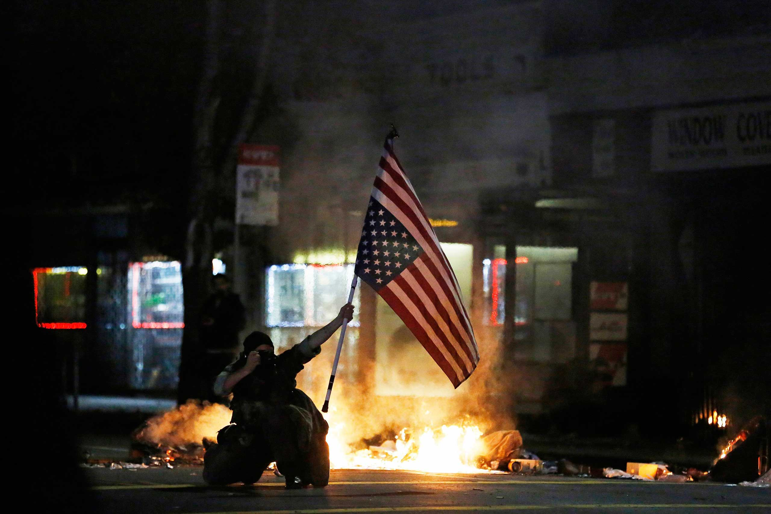 A demonstrator takes a photograph while holding an upside down U.S. flag during a demonstration in Berkeley, Calif. on Dec. 8, 2014.