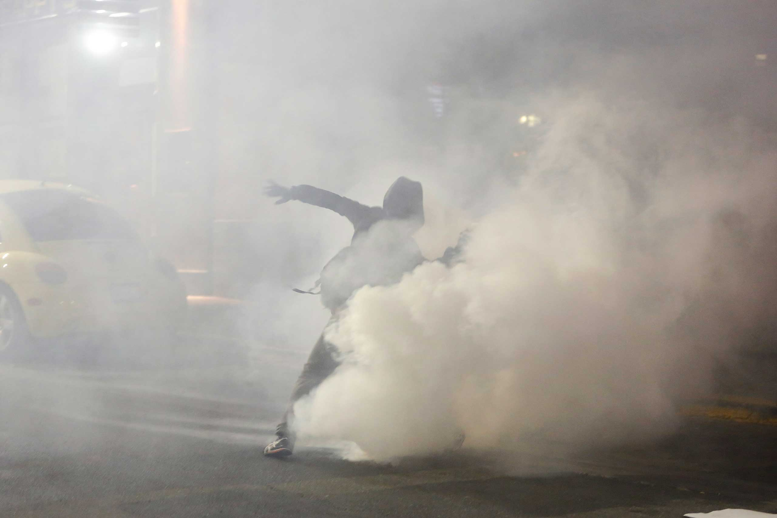 A demonstrator throws back a teargas canister toward the police line during the fourth night of demonstrations in Berkeley, Calif., Dec. 6, 2014.