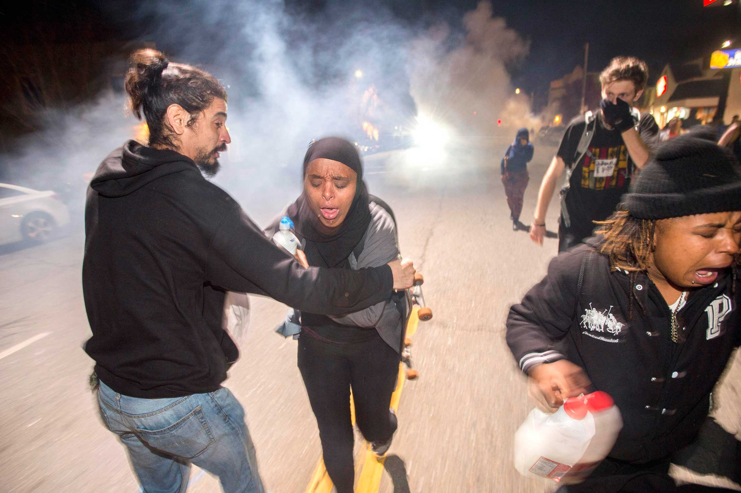 Protesters retreat while police officers deploy teargas to disperse a crowd comprised largely of student protesters in Berkeley, Calif. on Dec. 7, 2014.