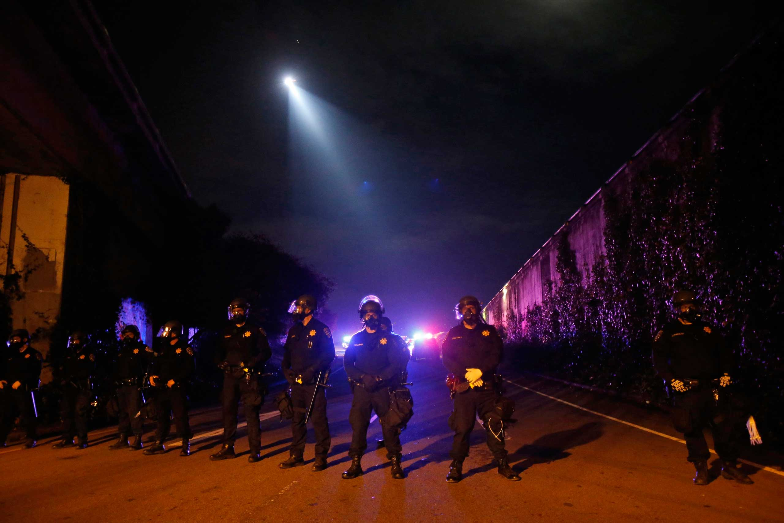 Members of the California Highway Patrol form a line on a freeway entrance after protesters ran onto Highway 24 in Berkeley, Calif. on Dec. 7, 2014.