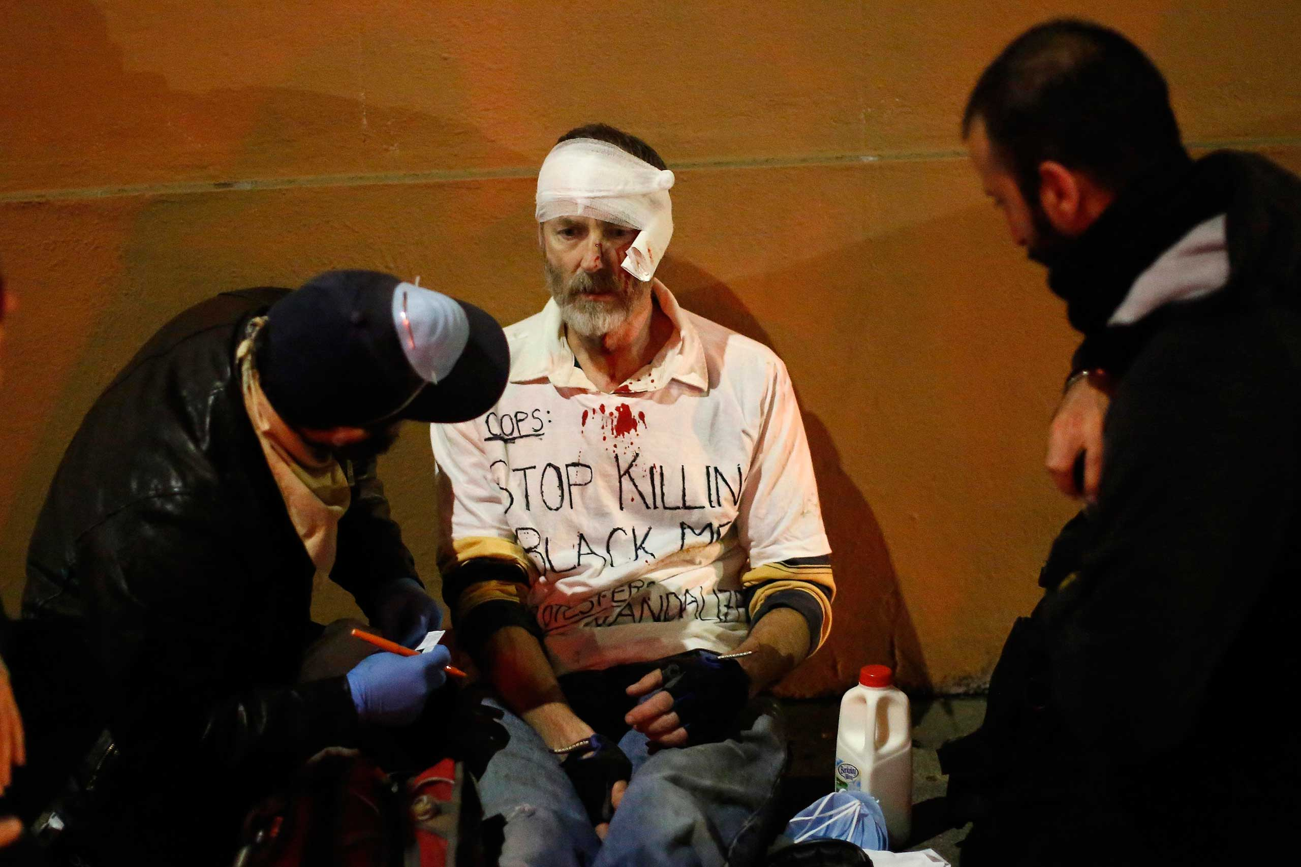 Medics tend to an injured protester after he was hit in the head while attempting to stop others from vandalizing a Radio Shack in Berkeley, Calif. on Dec. 7, 2014.
