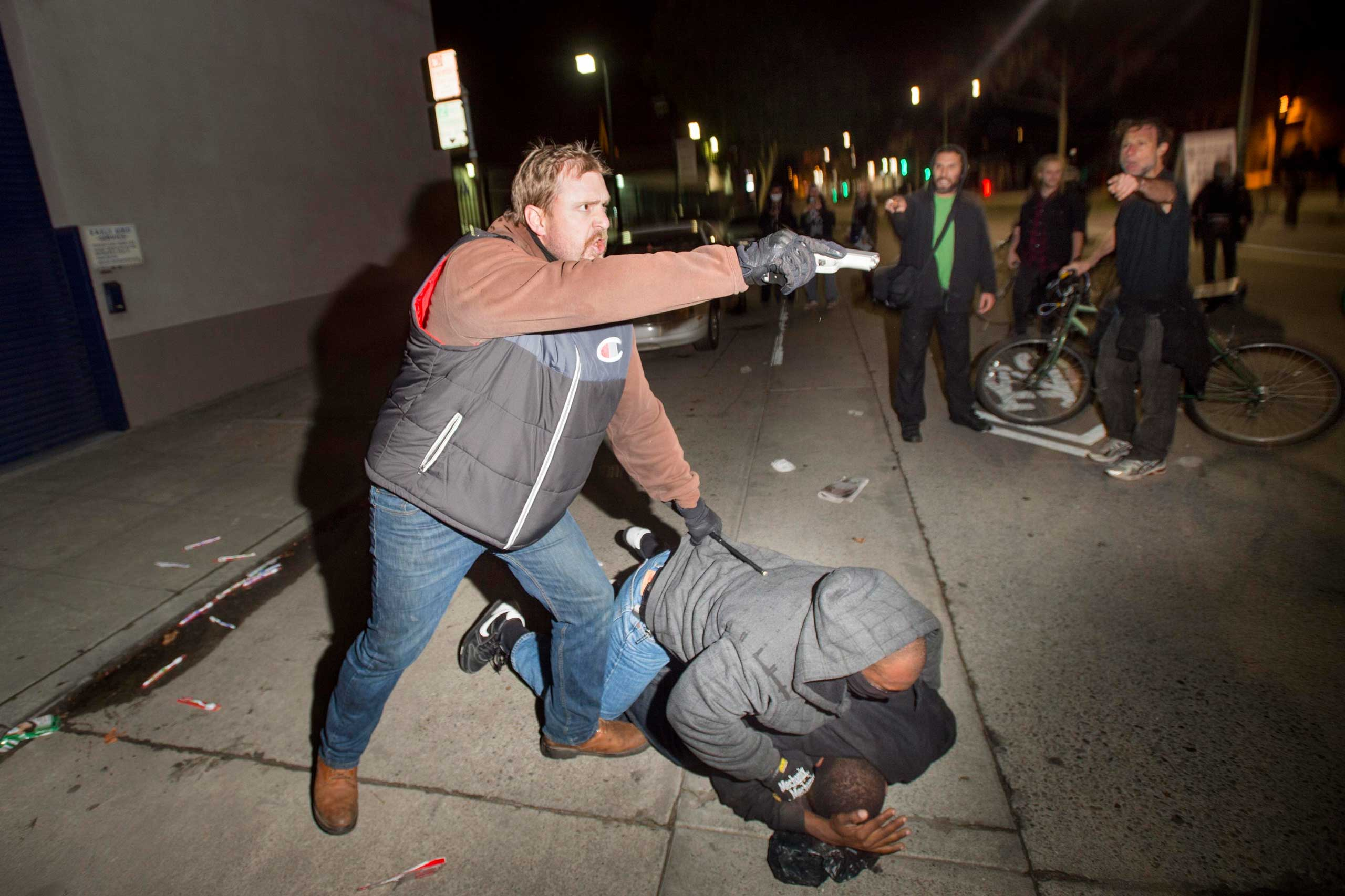 An undercover police officer aims his gun at protesters after some in the crowd attacked him and his partner in Oakland, Calif. on Dec. 10, 2014.