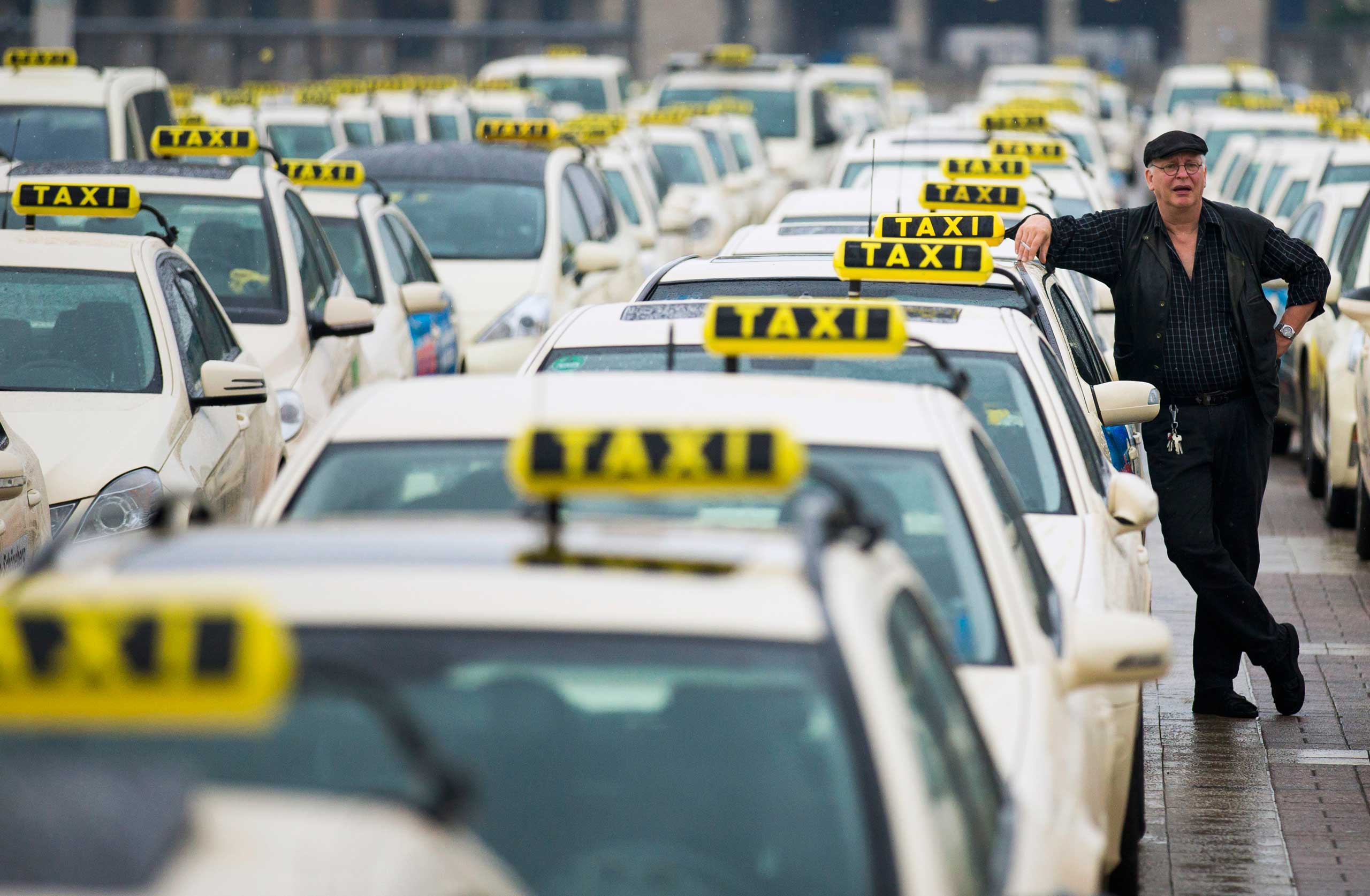 A taxi driver listens to speeches by his colleagues, during an Europe-wide protest of licensed taxi drivers against taxi hailing apps that are feared to flush unregulated private drivers into the market, in front of the Olympic stadium in Berlin on June 11, 2014.