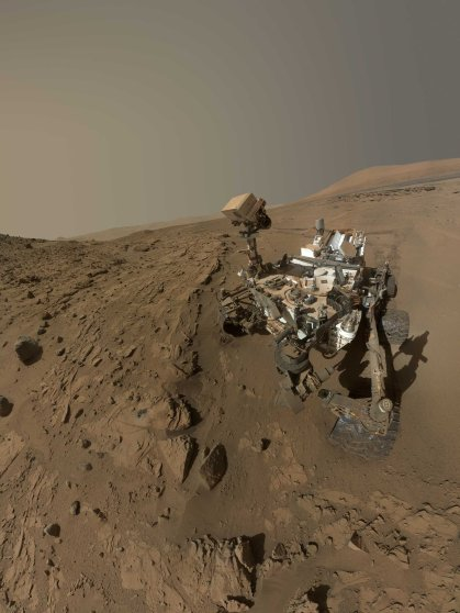 """NASA's Curiosity Mars rover used the camera at the end of its arm in April and May 2014 to take dozens of component images combined into this self-portrait where the rover drilled into a sandstone target called """"Windjana."""" The camera is the Mars Hand Lens Imager (MAHLI), which previously recorded portraits of Curiosity at two other important sites during the mission: """"Rock Nest"""" (http://photojournal.jpl.nasa.gov/catalog/PIA16468) and """"John Klein"""" (http://photojournal.jpl.nasa.gov/catalog/PIA16937).Winjana is within a science waypoint site called """"The Kimberley,"""" where sandstone layers with different degrees of resistance to wind erosion are exposed close together.The view does not include the rover's arm. It does include the hole in Windjana produced by the hammering drill on Curiosity's arm collecting a sample of rock powder from the interior of the rock. The hole is surrounded by grayish cuttings on top of the rock ledge to the left of the rover. The Mast Camera (Mastcam) atop the rover's remote sensing mast is pointed at the drill hole. A Mastcam image of the drill hole from that perspective is at http://mars.jpl.nasa.gov/msl/multimedia/raw/?rawid=0626MR0026780000401608E01_DXXX&s=626. The hole is 0.63 inch (1.6 centimeters) in diameter. The rover's wheels are 20 inches (0.5 meter) in diameter.Most of the component frames of this mosaic view were taken during the 613th Martian day, or sol, of Curiosity's work on Mars (April 27, 2014). Frames showing Windjana after completion of the drilling were taken on Sol 627 (May 12, 2014). The hole was drilled on Sol 621 (May 5, 2014).MAHLI was built by Malin Space Science Systems, San Diego. NASA's Jet Propulsion Laboratory, a division of the California Institute of Technology in Pasadena, manages the Mars Science Laboratory Project for the NASA Science Mission Directorate, Washington. JPL designed and built the project's Curiosity rover.> NASA's Mars Curiosity Rover Marks First Martian Year with Mission Suc"""