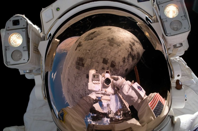 Astronaut Stephen K. Robinson, STS-114 mission specialist, used a digital camera to expose a photo of his helmet visor during the third Extravehicular Activity EVA of the mission. Also visible in the reflection are thermal protection tiles on Space Shuttle Discovery's under Aug. 3, 2005.