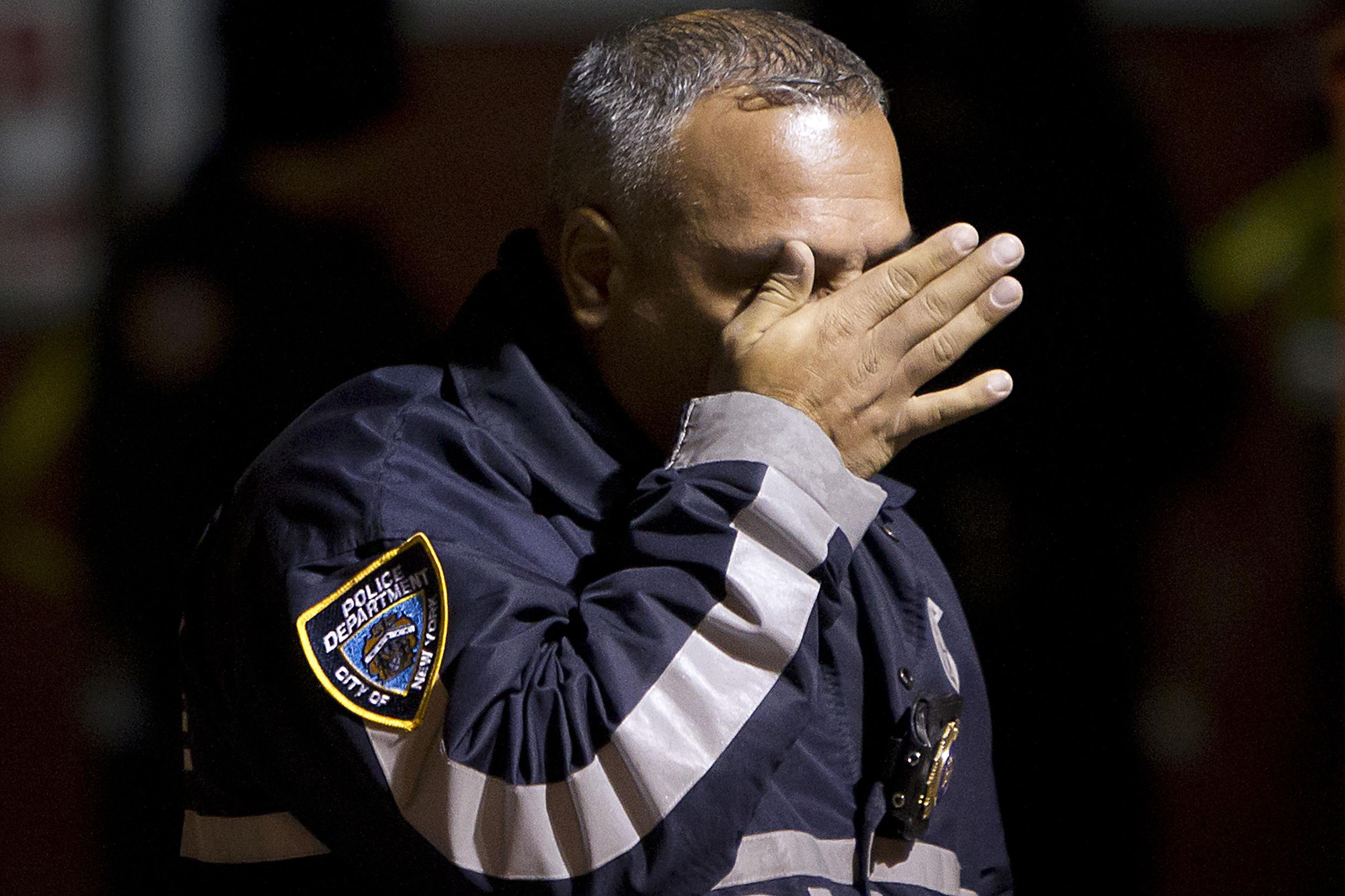 A police officer wipes tears away from his face as he walks away from the scene of a shooting where two New York Police officers were shot dead in the Brooklyn borough of New York City on Dec.  20, 2014.