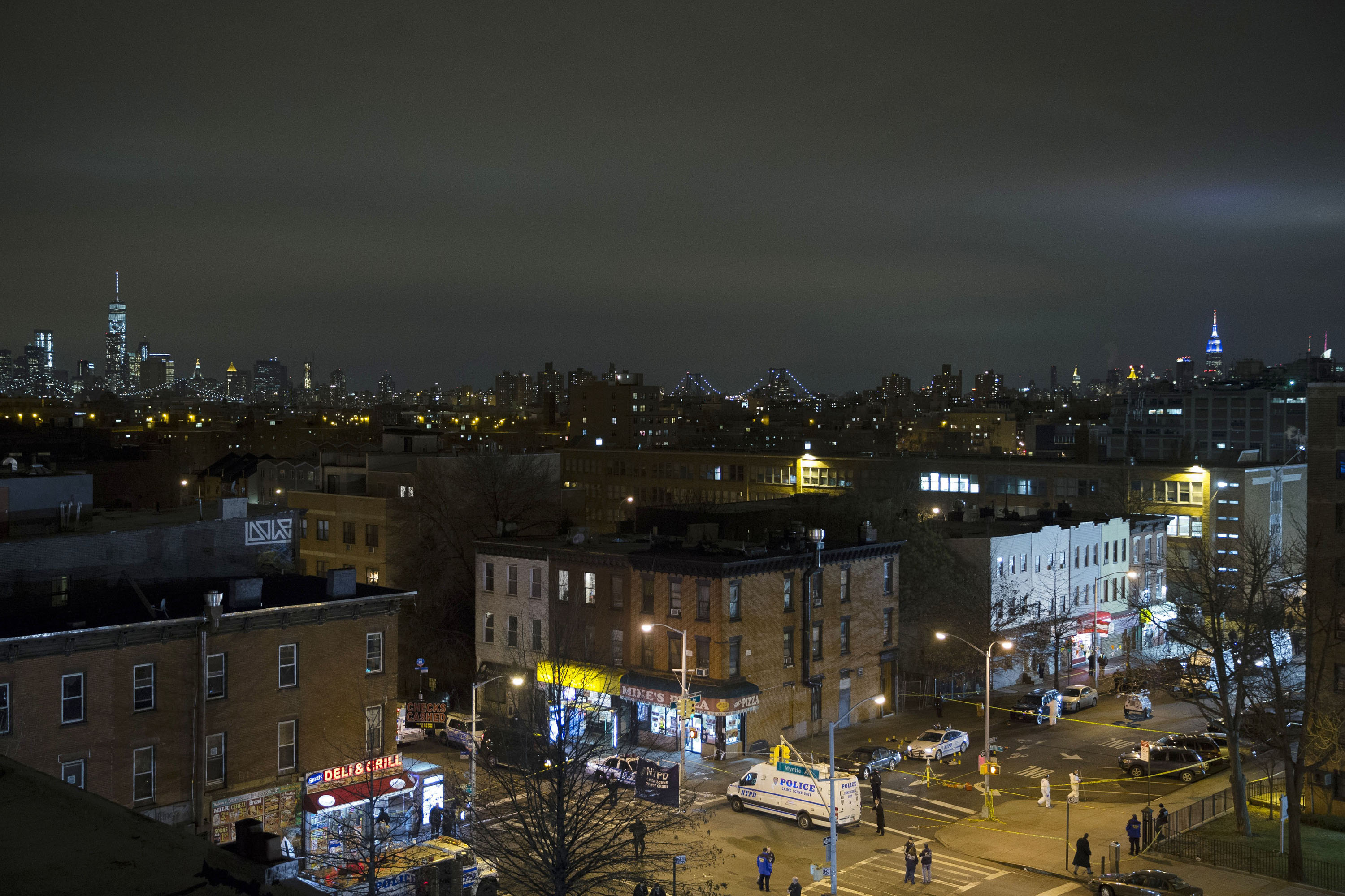 The skyline of Manhattan is seen in the background as investigators work at the scene where two NYPD officers were shot in the Brooklyn borough of New York City on Dec. 20, 2014