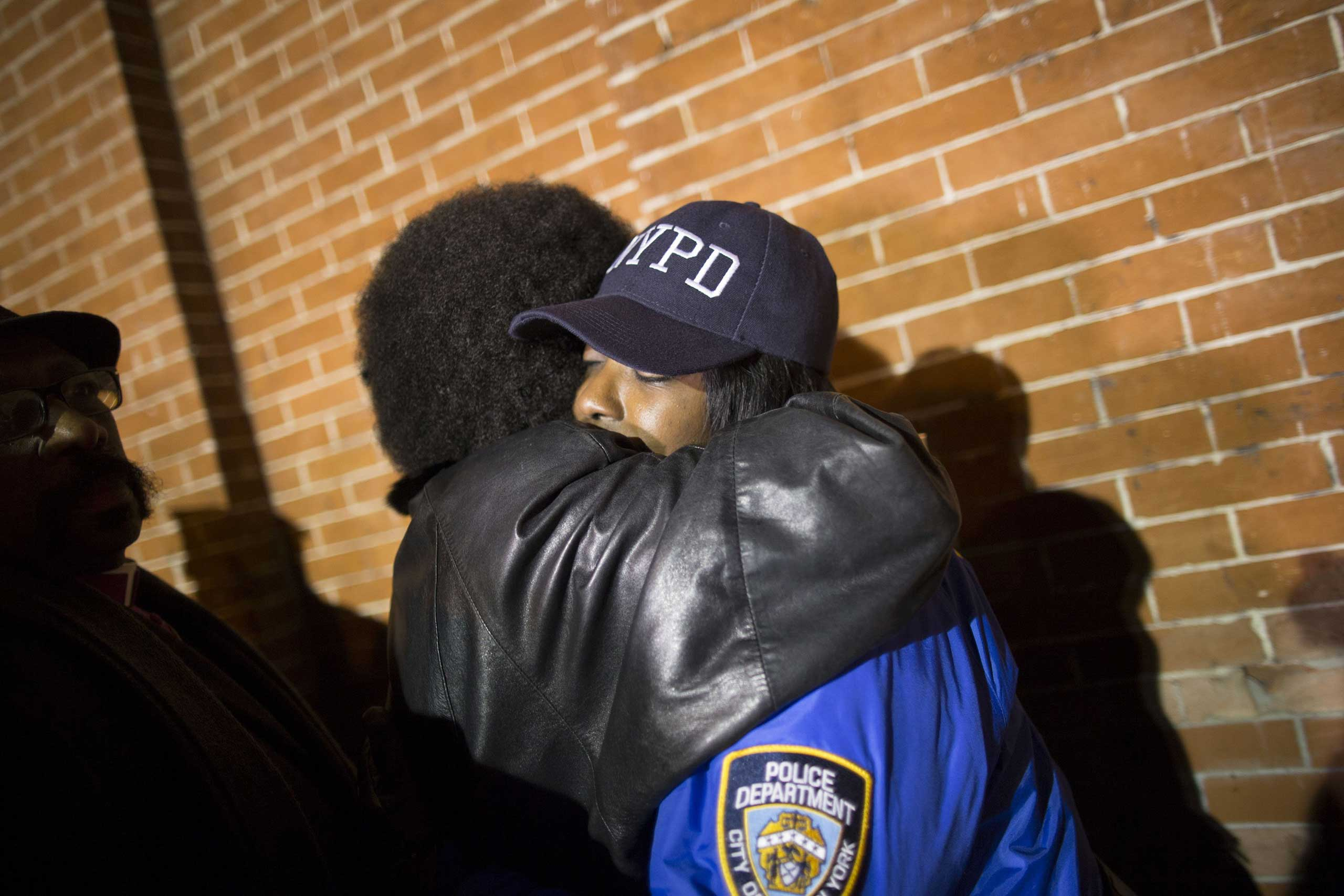 Mourners take part in a prayer vigil at the site where two police officers were fatally shot in the Brooklyn borough of New York City, Dec. 21, 2014.