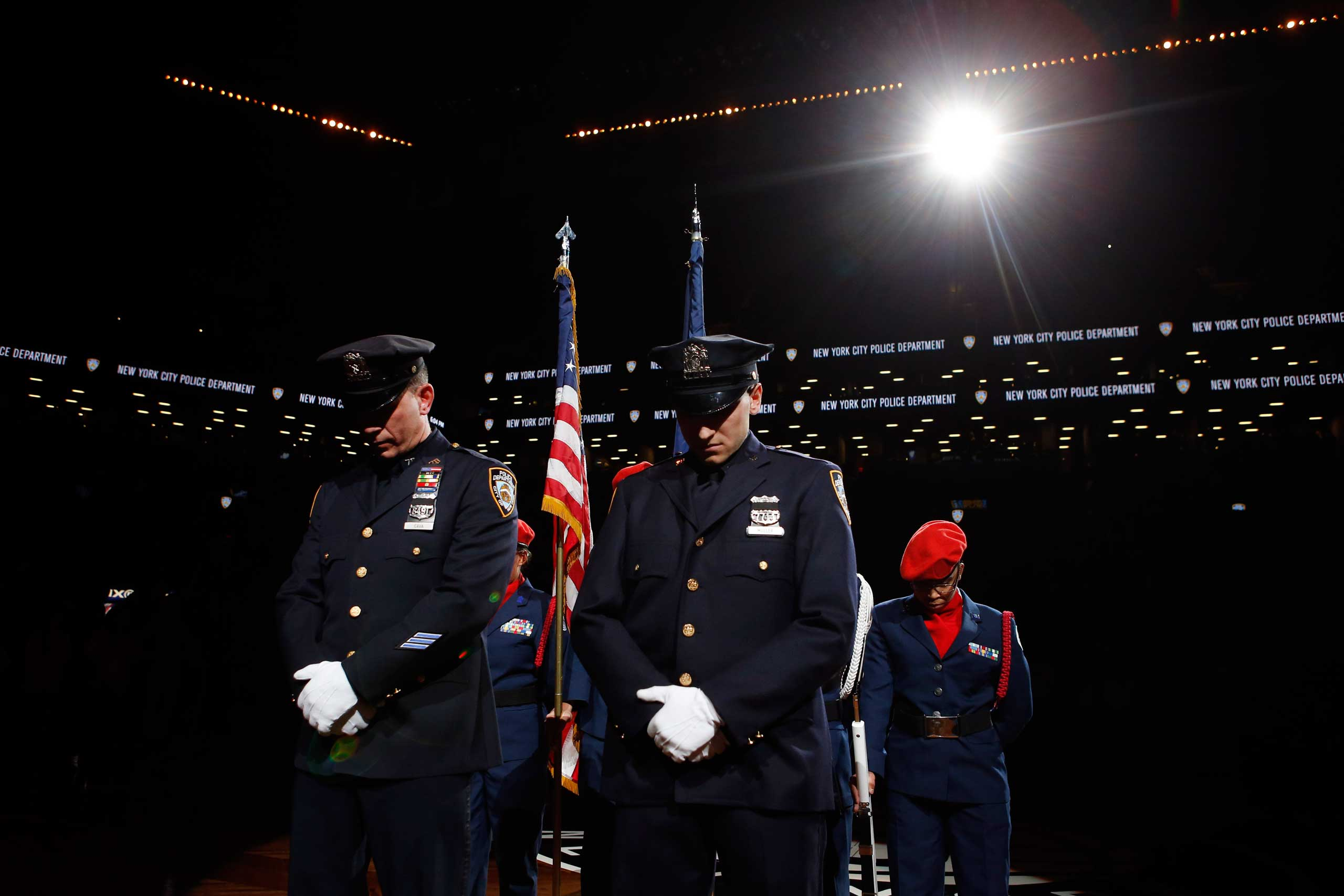 New York Police Department officers Mark Cava, left, and Jason Muller participate in a moment of silence for two slain NYPD officers before an NBA basketball game between the Brooklyn Nets and the Detroit Pistons on Dec. 21, 2014, in New York City.
