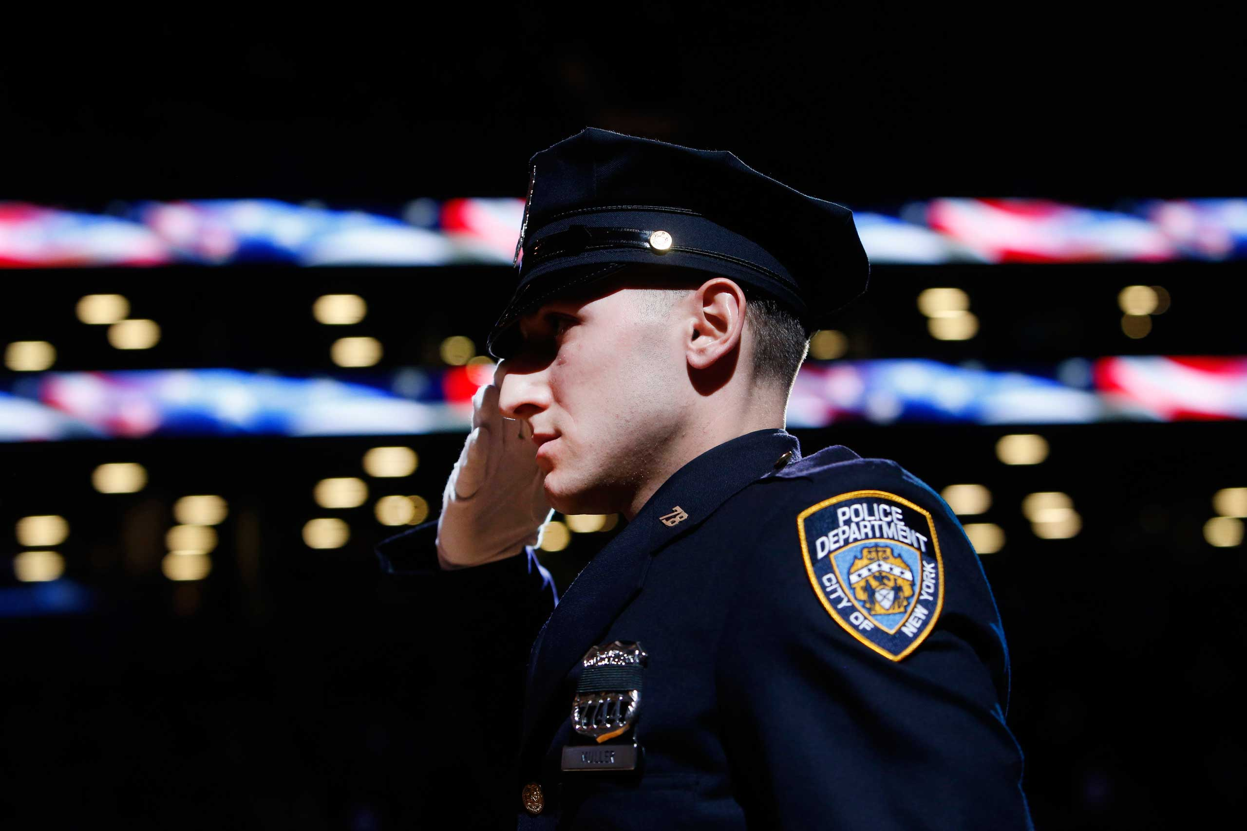 New York Police Department officer Jason Muller salutes during the national anthem after participating in a moment of silence for two slain NYPD officers before an NBA basketball game between the Brooklyn Nets and the Detroit Pistons in New York City on Dec. 21, 2014.