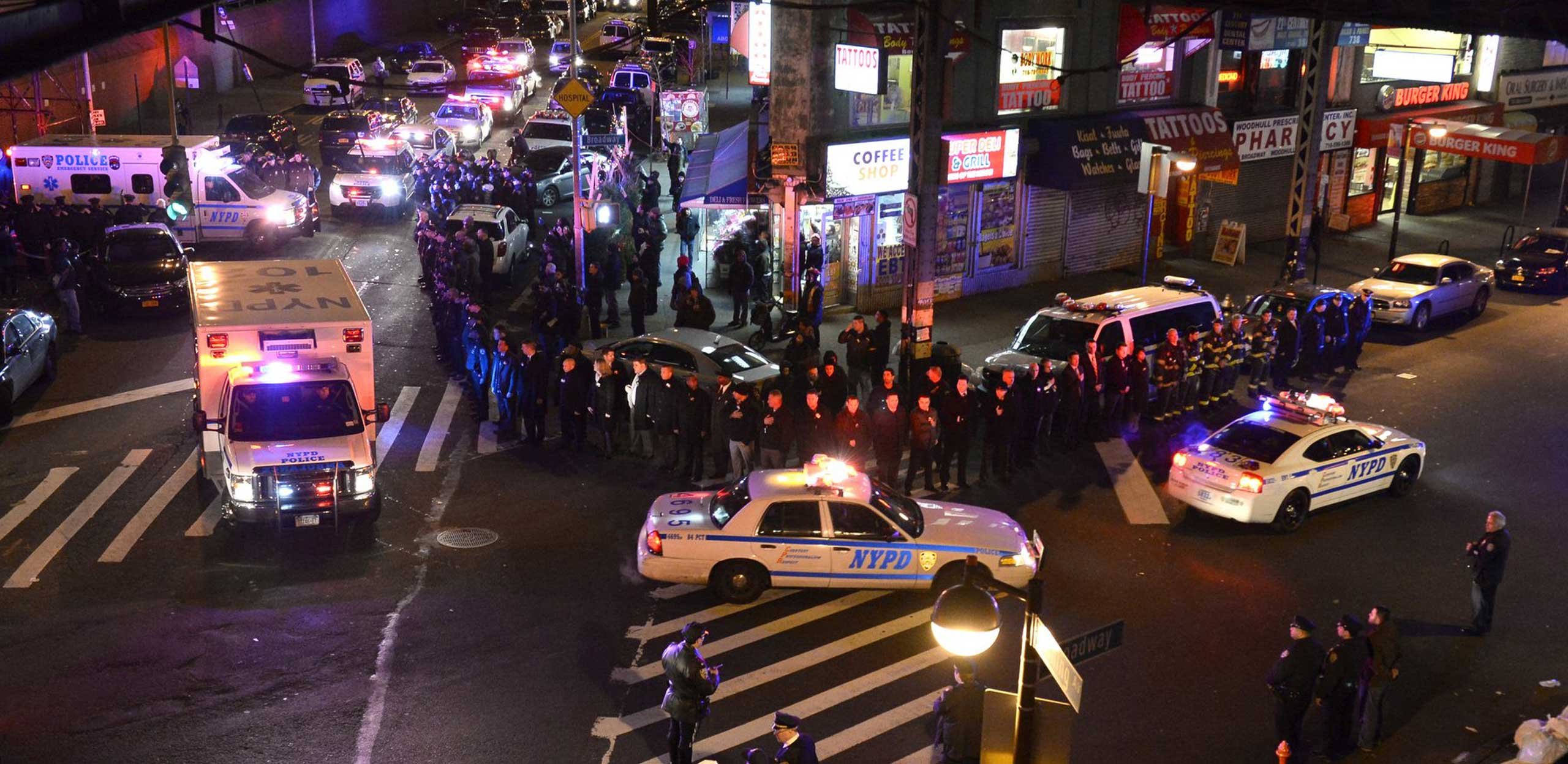 Police pay their respect outside Woodhull Hospital as two Police ambulances carrying the bodies of two murdered officers head to Bellevue Hospital in New York City, Dec. 20, 2014.