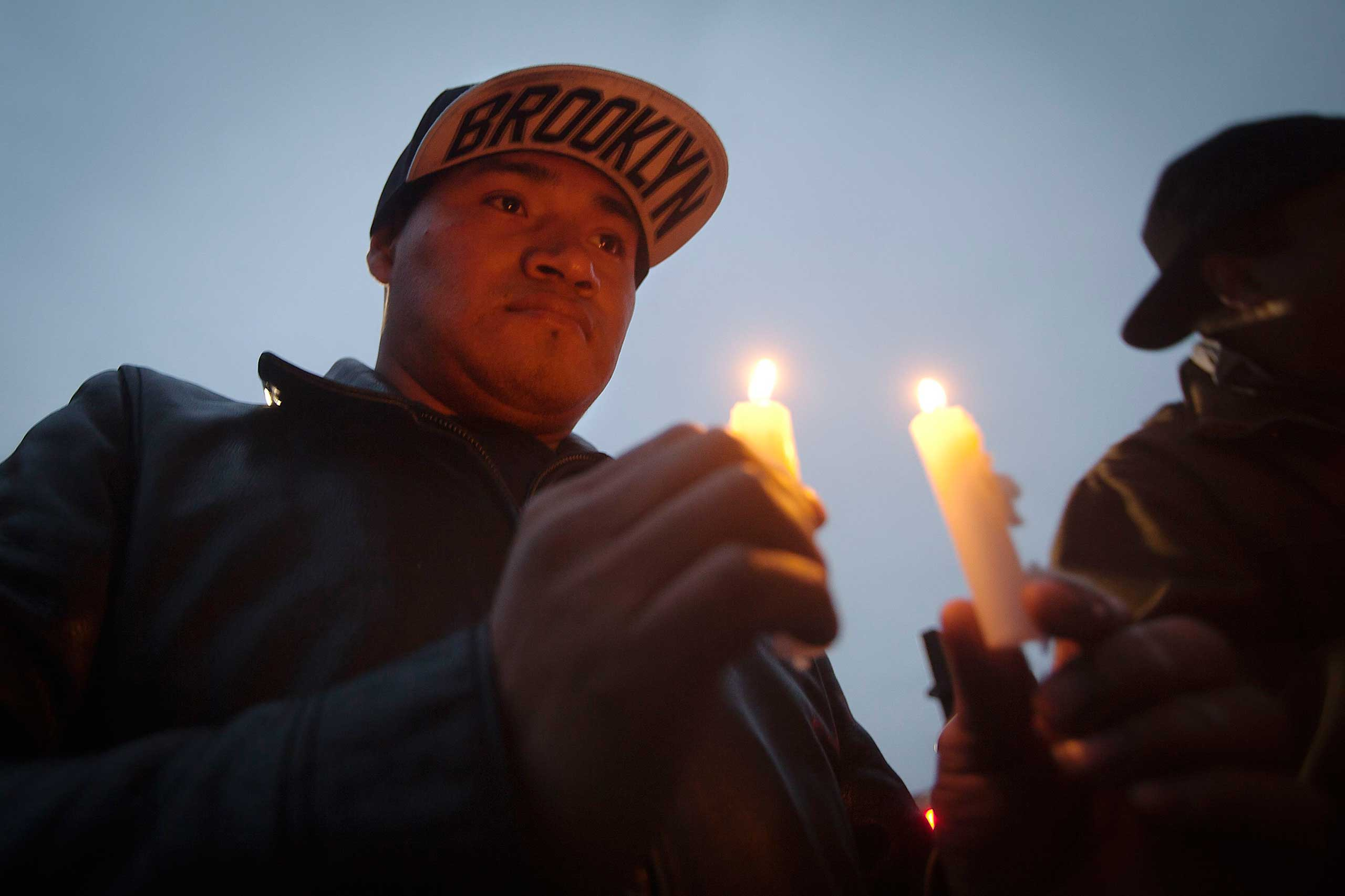 A man takes part in a prayer vigil at the site where two police officers were fatally shot in the Brooklyn borough of New York City, Dec. 21, 2014.