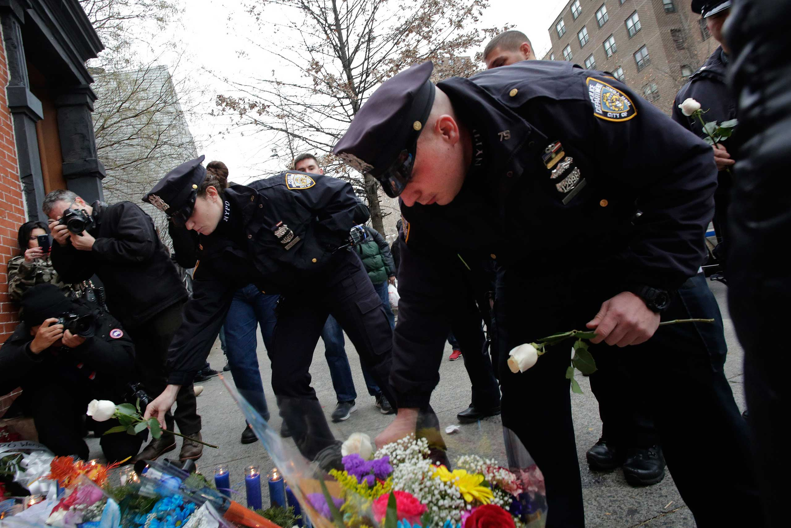 New York City police officer Darren Cox, right, accompanied by fellow officers, leaves flowers at a memorial in the Brooklyn borough of New York City on Dec. 21, 2014.