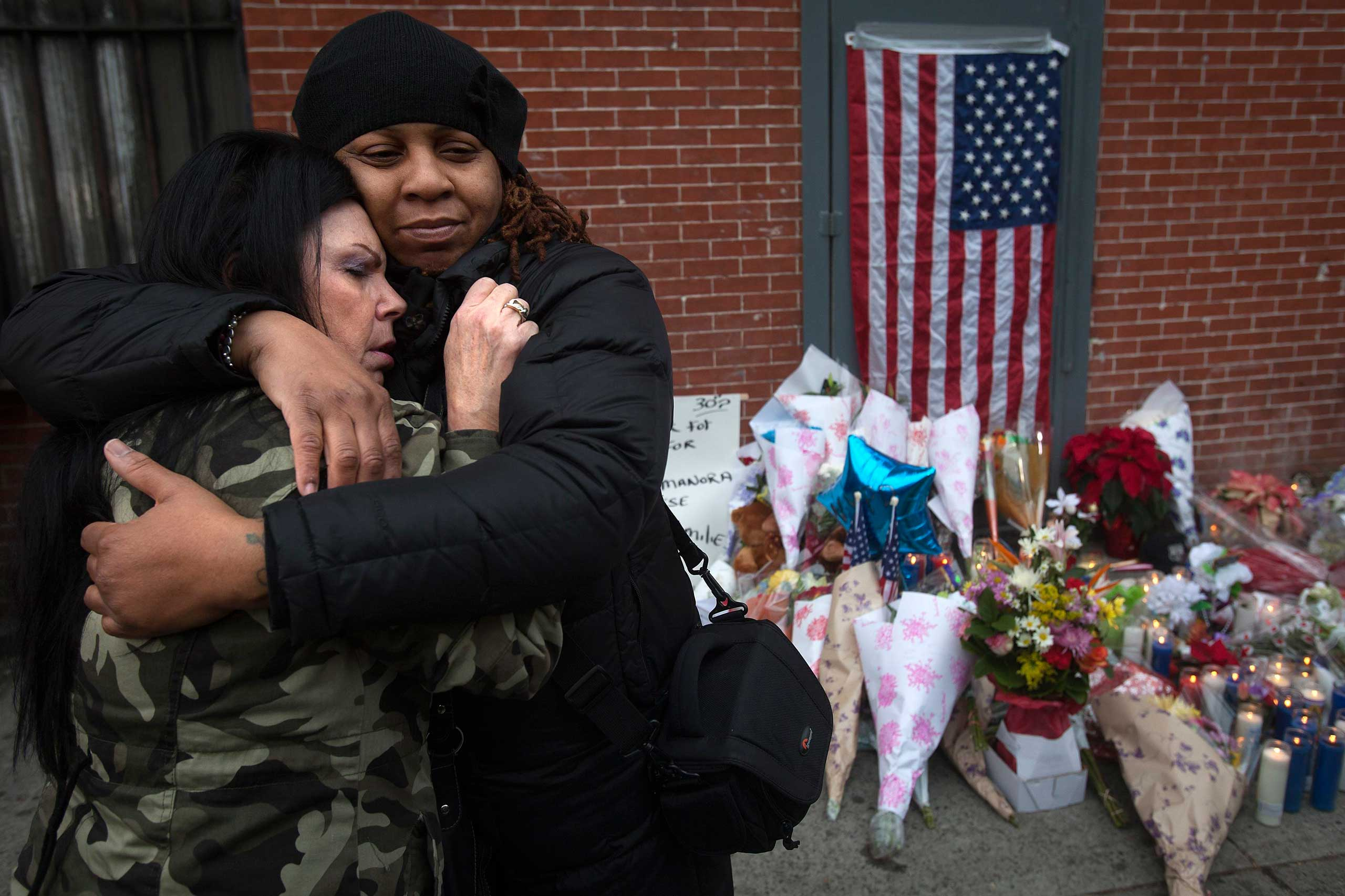 Donna Salvaggio (L) and a woman who gave her name as Reverend Jordan hug at a makeshift memorial at the site where two police officers were shot in the Brooklyn borough of New York City, Dec. 21, 2014.