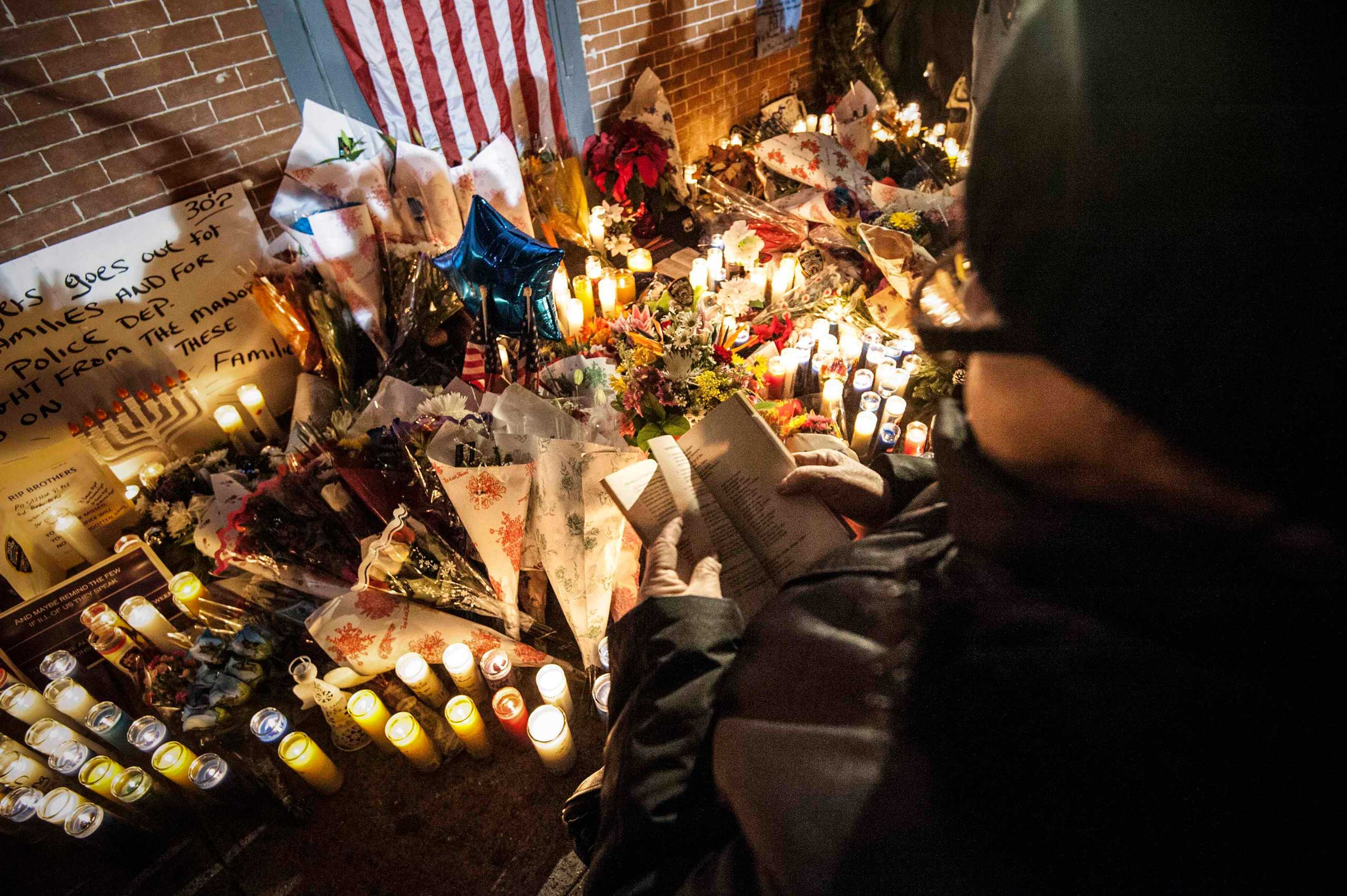 A woman recites from a Bible while standing over a makeshift memorial during a prayer vigil at the site where two  New York Police Department (NYPD)  officers were fatally shot in the Brooklyn borough of New York City, Dec.  21, 2014.