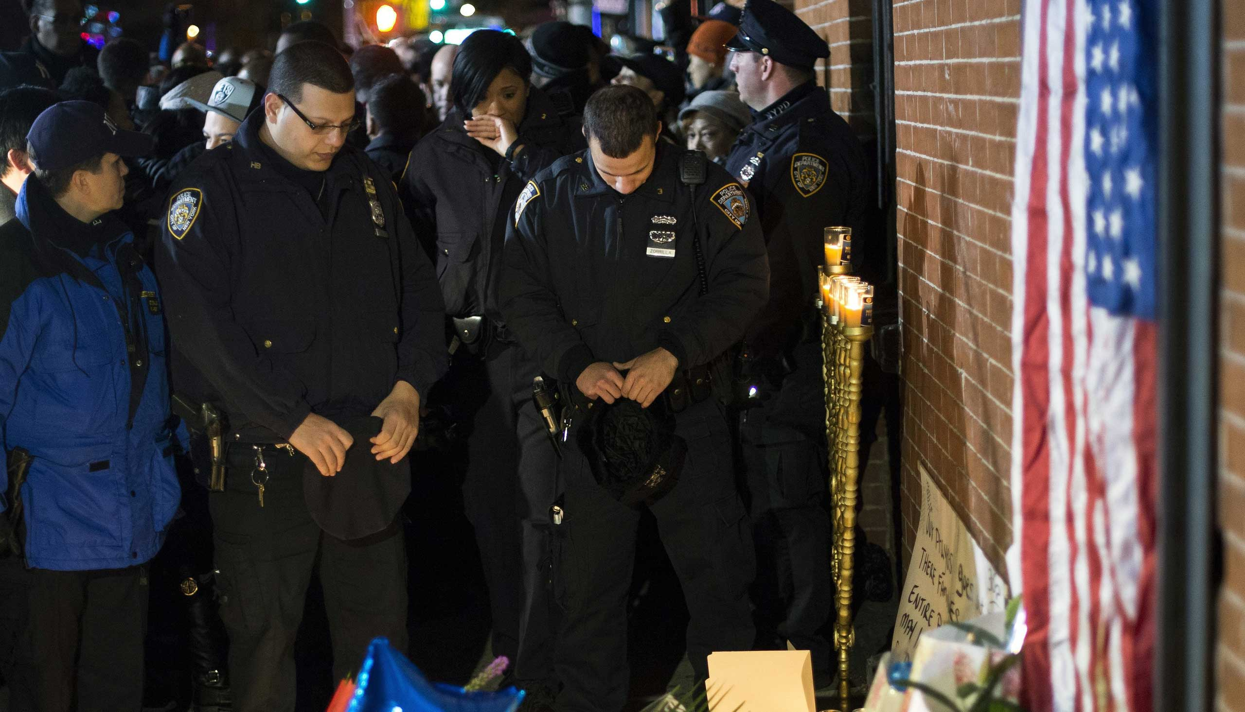 Police officers pause in front of a memorial for two police officers who were killed in Brooklyn, New York City, on Dec. 21, 2014.