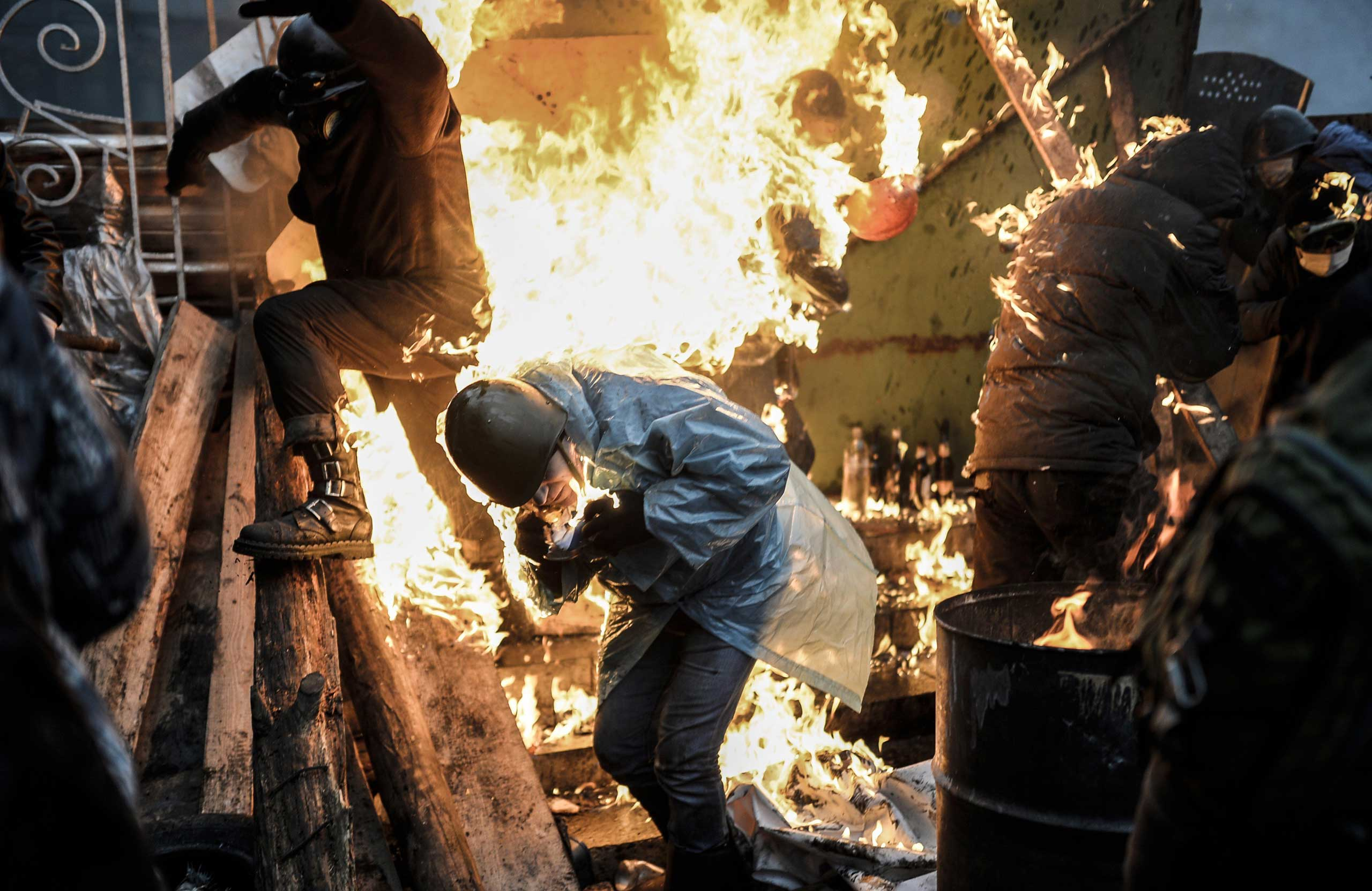Protesters burn as they stand behind burning barricades during clashes with police on February 20, 2014 in Kiev, Ukraine.