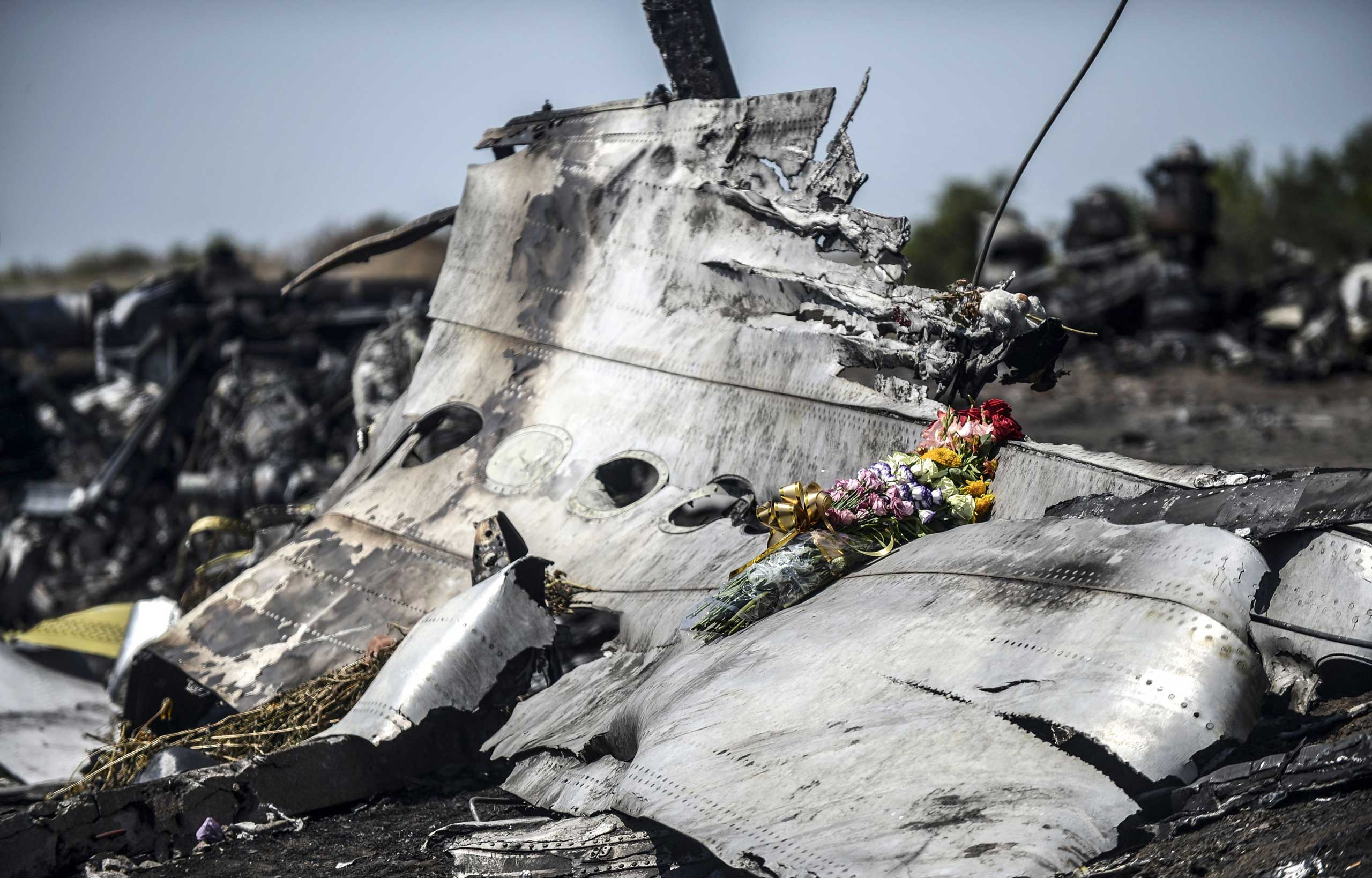This photo taken on July 26, 2014 shows flowers left by parents of an Australian victim of the Malaysia Airlines Flight 17 crash, laid on a piece of the plane, near the village of Hrabove (Grabovo), in the Donetsk region of Ukraine.