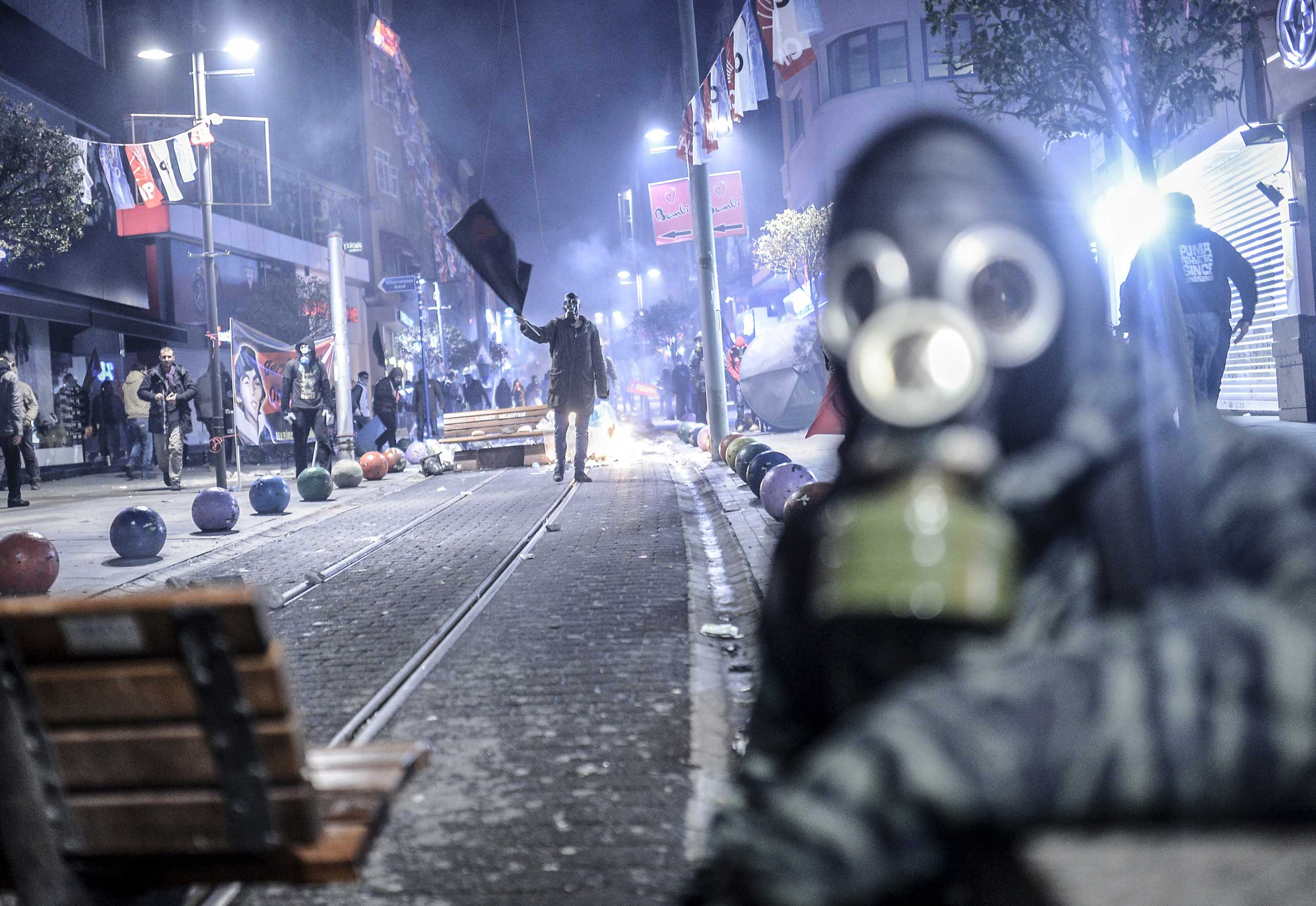 A protester waves a black flag during clashes with riot police in Kadikoy, on the Anatolian side of Istanbul, on March 11, 2014.