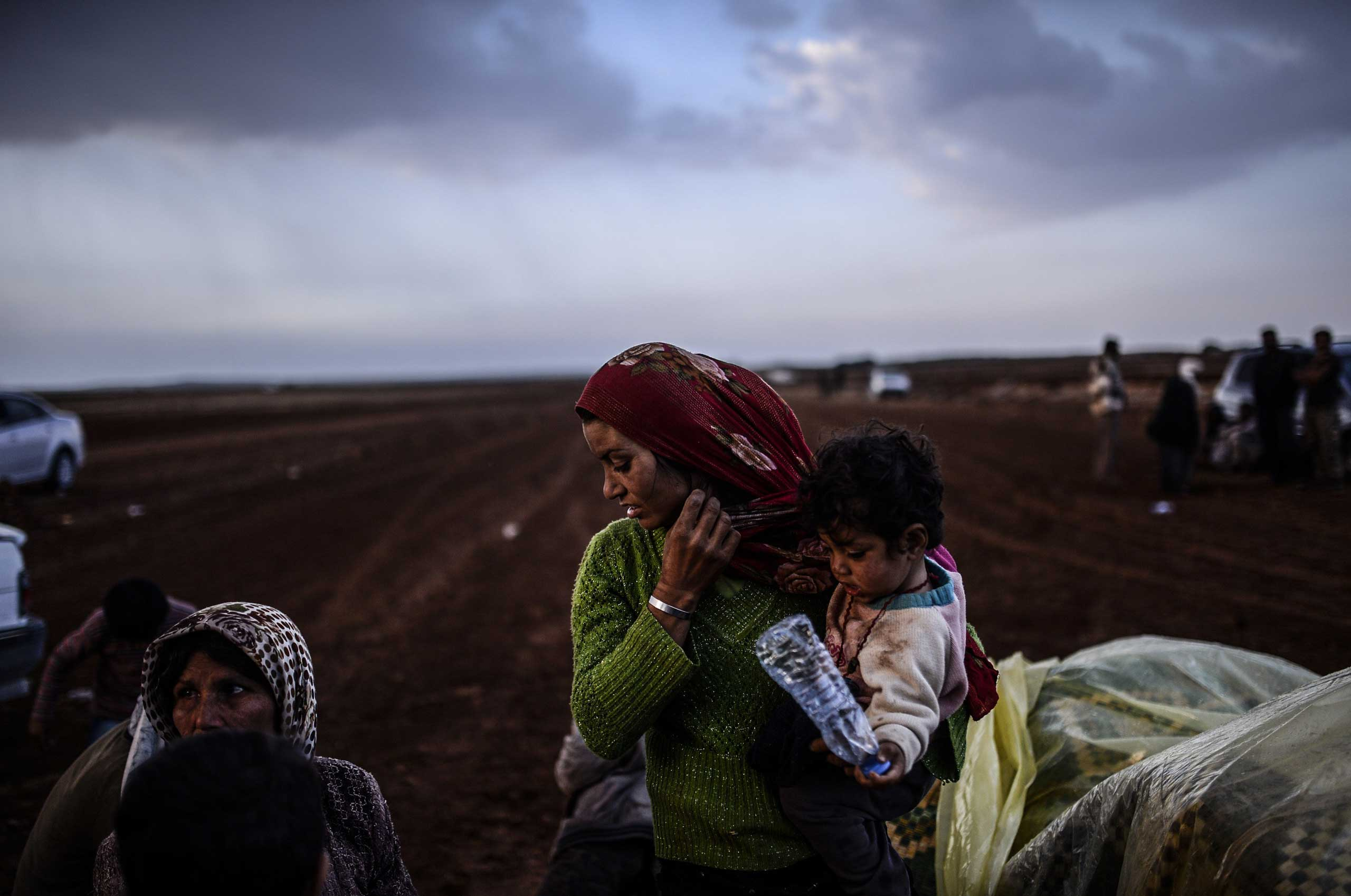 Syrian Kurds wait near the southeastern town of Suruc in the Sanliurfa province after crossing the border between Syria and Turkey on Oct. 2, 2014.