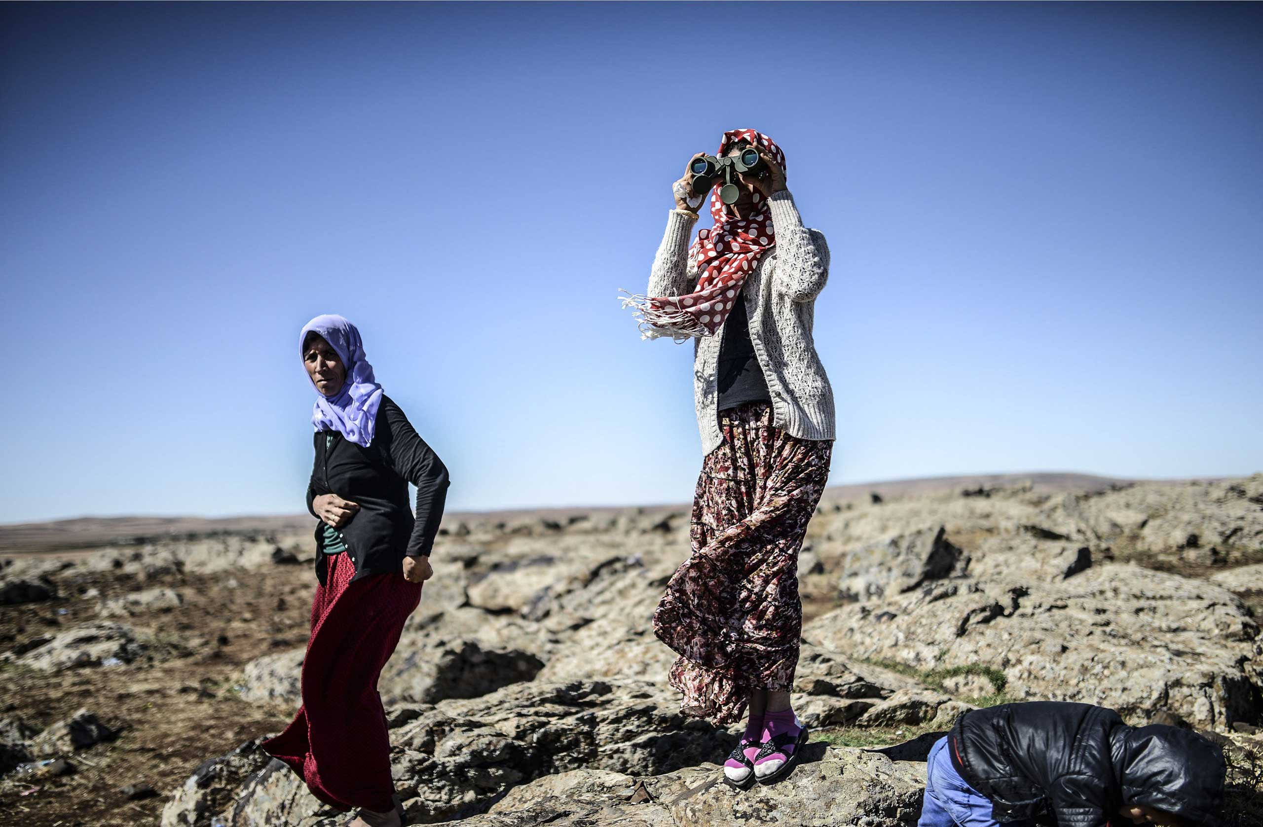 Members of the Syrian Kurdish Altay family try to spot their relative, Zamani Suruc, who is fighting Islamic State (IS) jihadists in the Syrian border town of Kobani on Oct. 20, 2014.