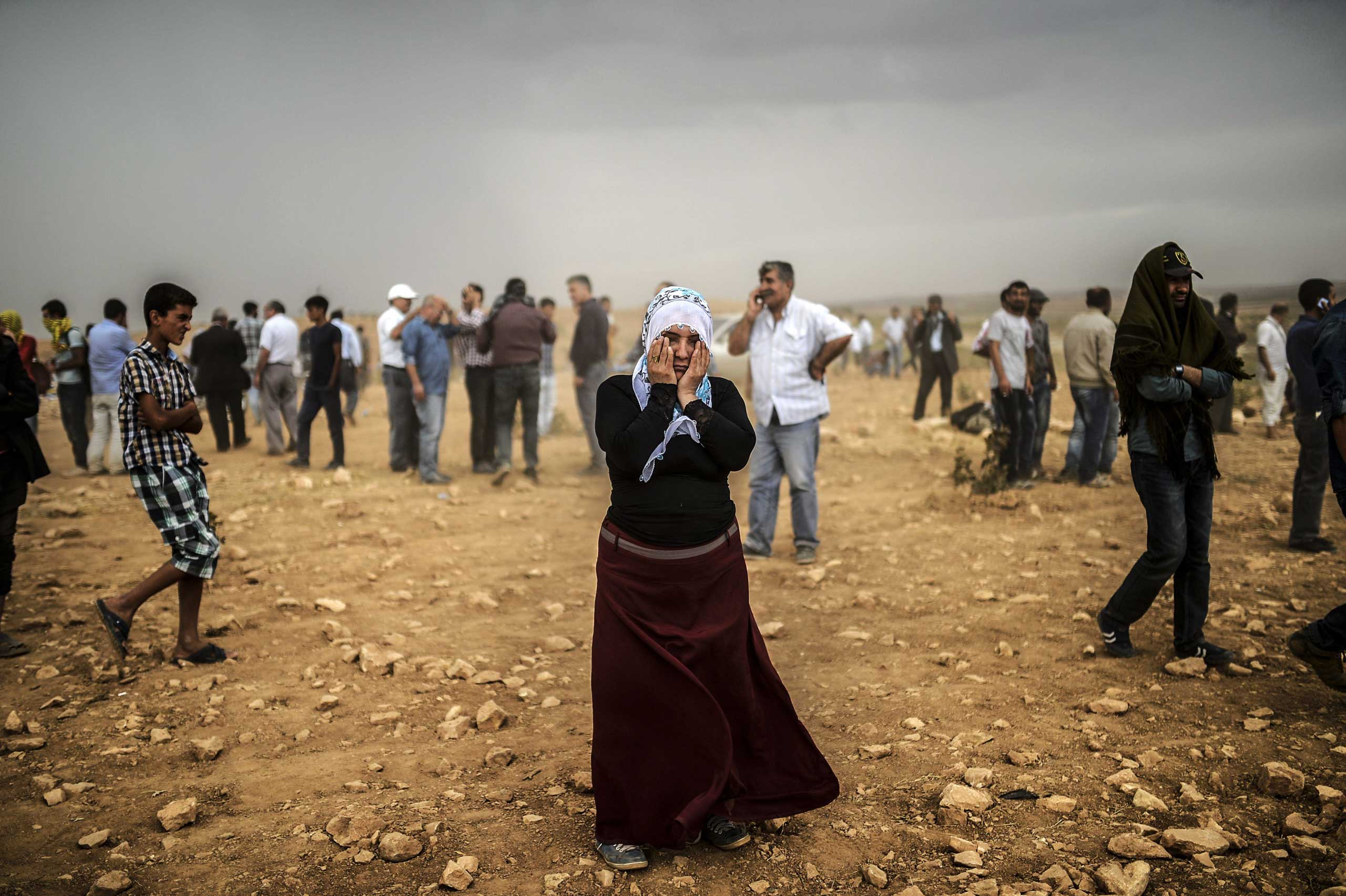 A Syrian Kurdish woman wipes her eyes during a dust storm on a hill where she and others stand watching clashes between jihadists of the Islamic State (IS) and Kurdish fighters, at Swedi village in Sanliurfa province, Turkey, on Sept. 24, 2014.