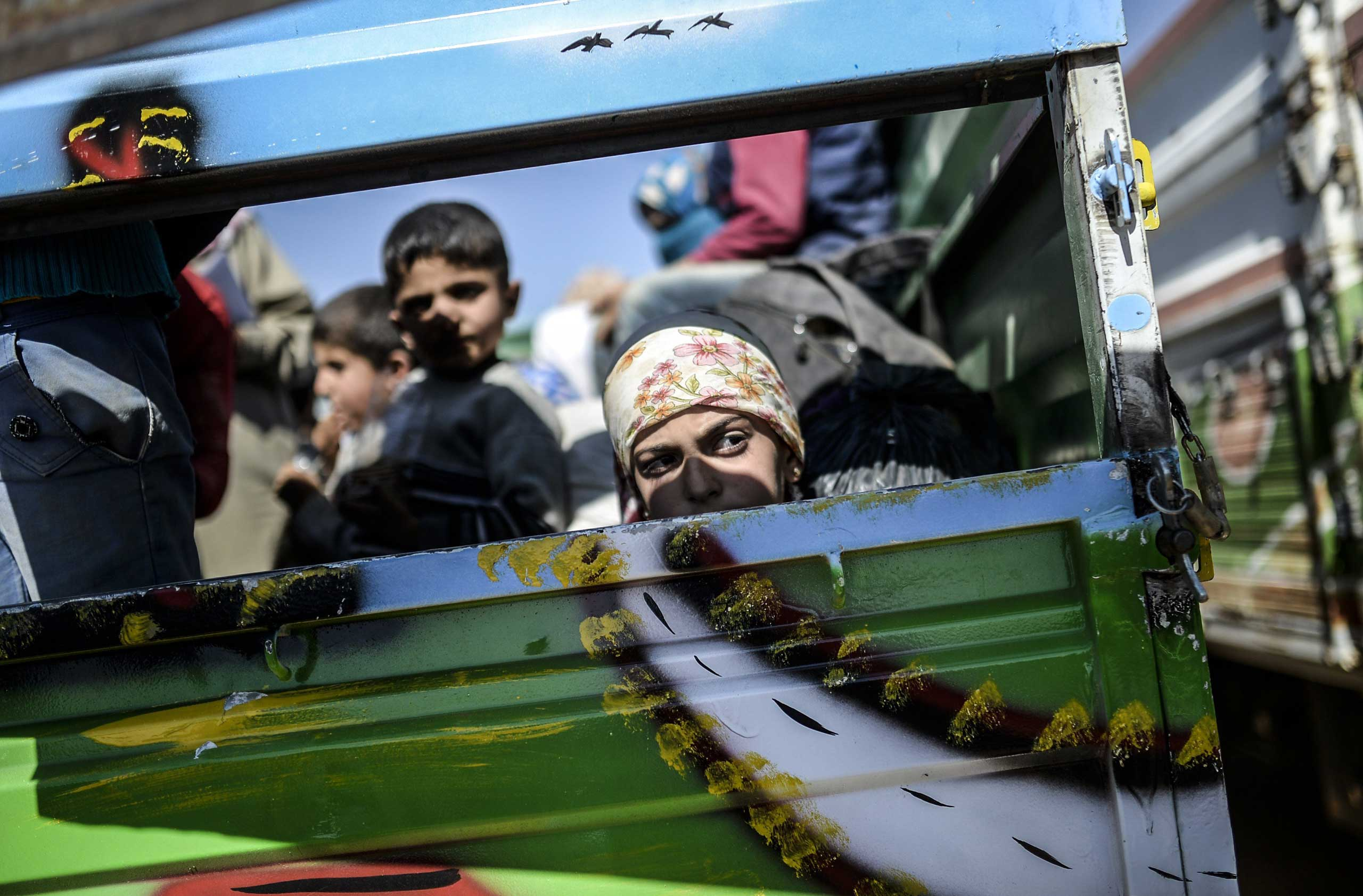 Syrian Kurds sit in a truck after crossing the Syrian-Turkish border in the southeastern town of Suruc in Sanliurfa province on Sept. 23, 2014.