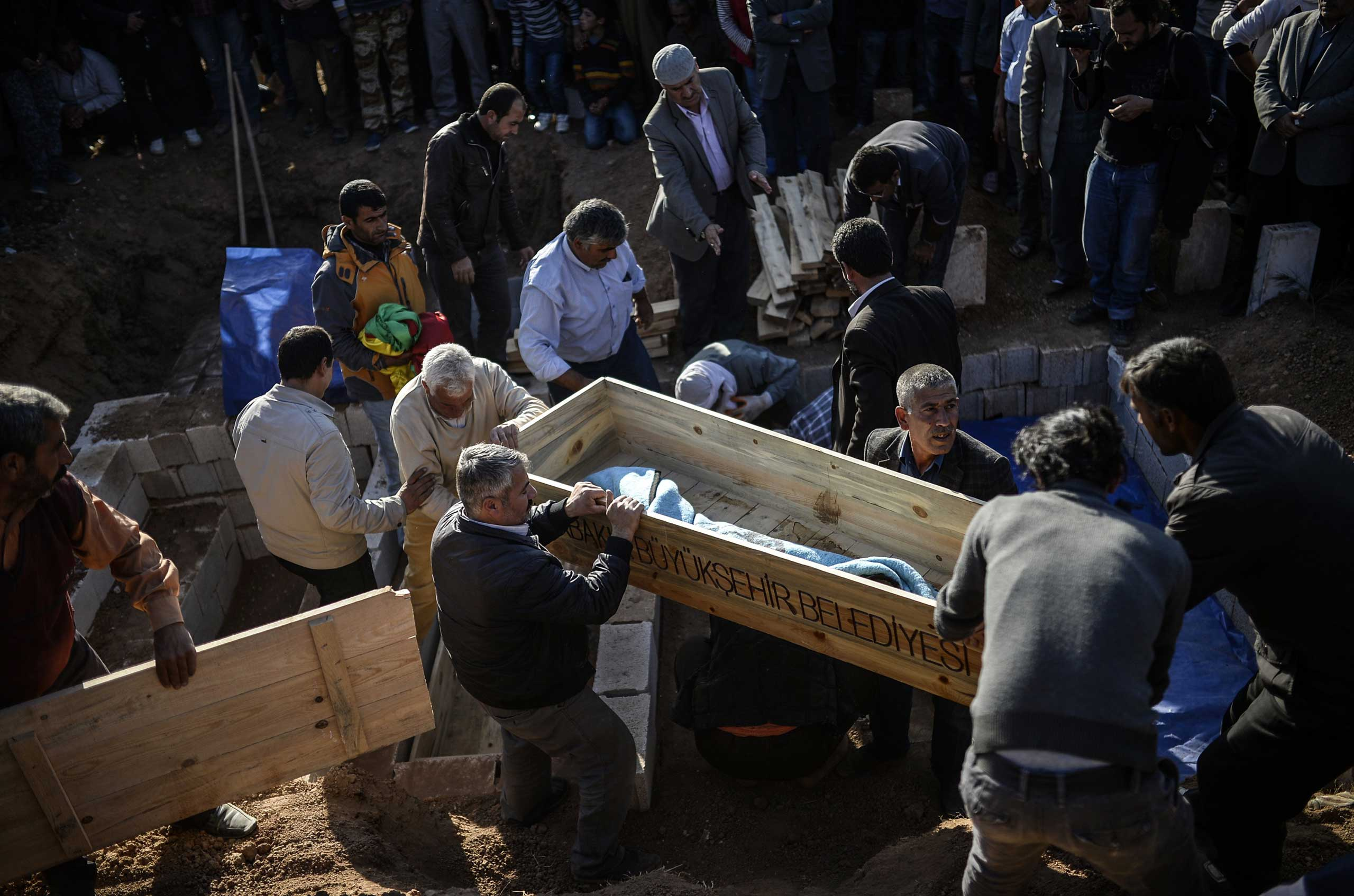 Men carry a coffin at a cemetery in Suruc, in the province of Sanliurfa, on Oct. 23, 2014, during the funeral of three Kurdish fighters who died in clashes with the Islamic State (IS) in neighbouring Syria.